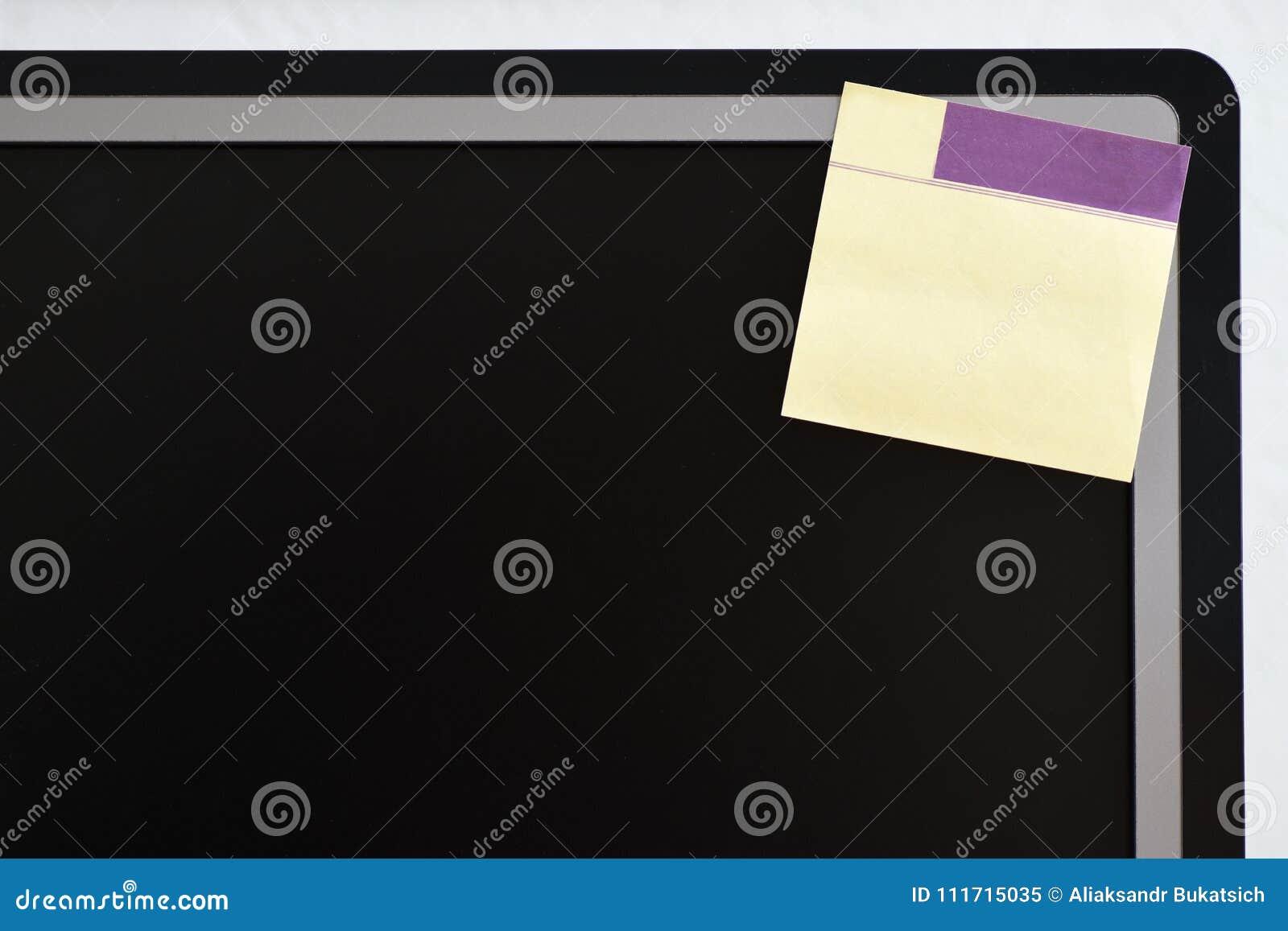 在显示器屏幕的角落的纸备忘录贴纸