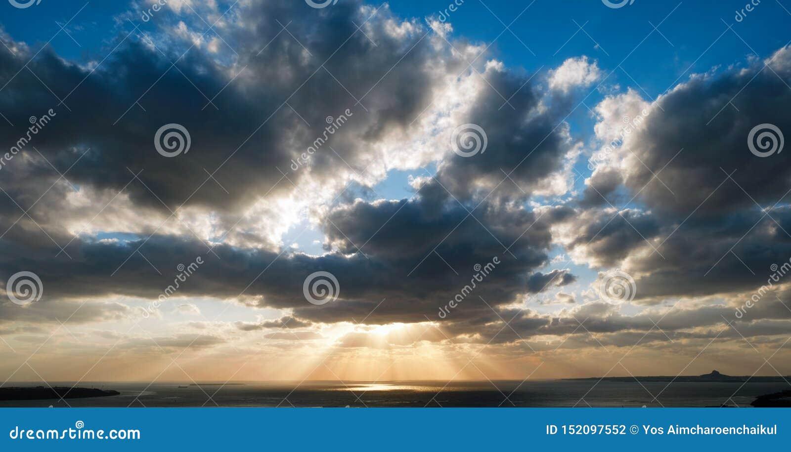 在晚上期间,太阳在云彩后落 太阳光芒早晨击穿云彩