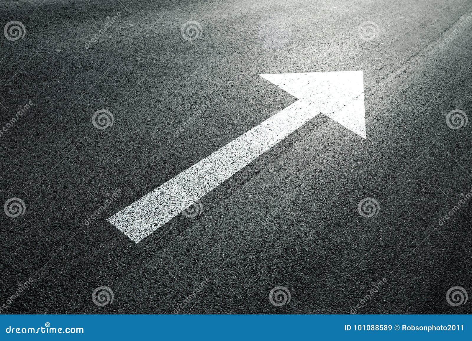 在晴朗的柏油路地板上的箭头标志
