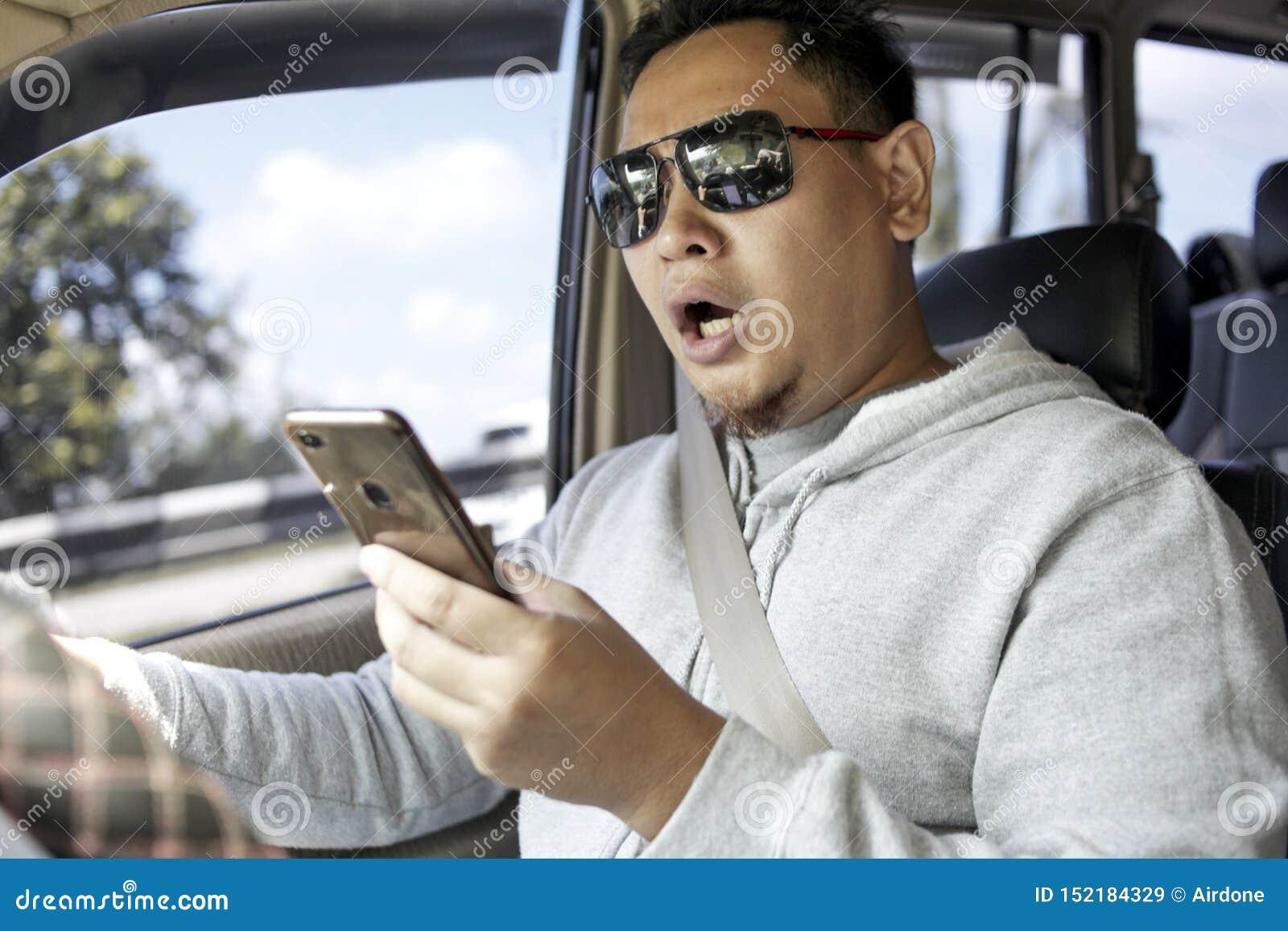 在智能手机的男性司机读书消息,当驾驶汽车时