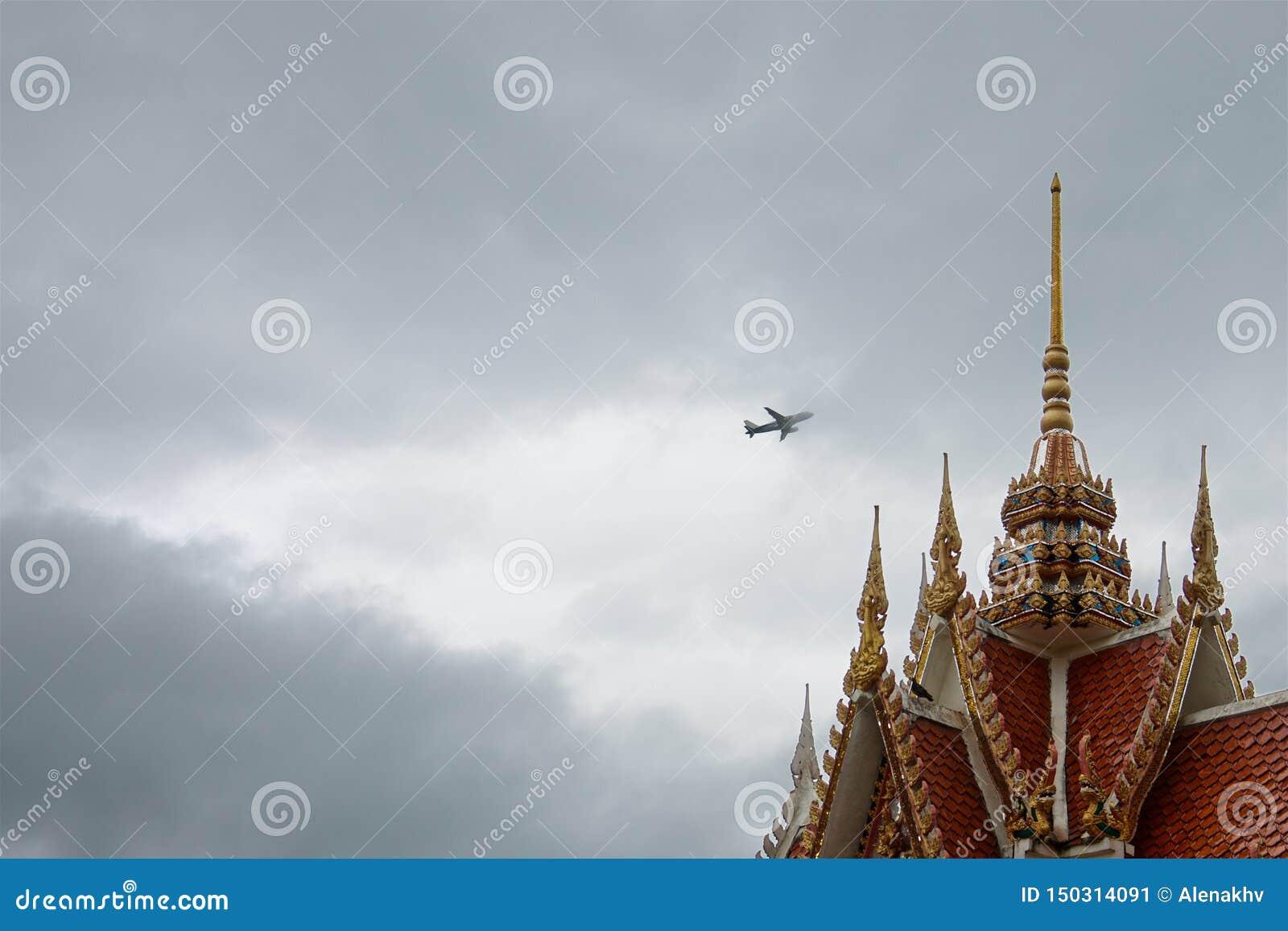 在暴风云的飞机在一个五颜六色的老泰国寺庙的屋顶