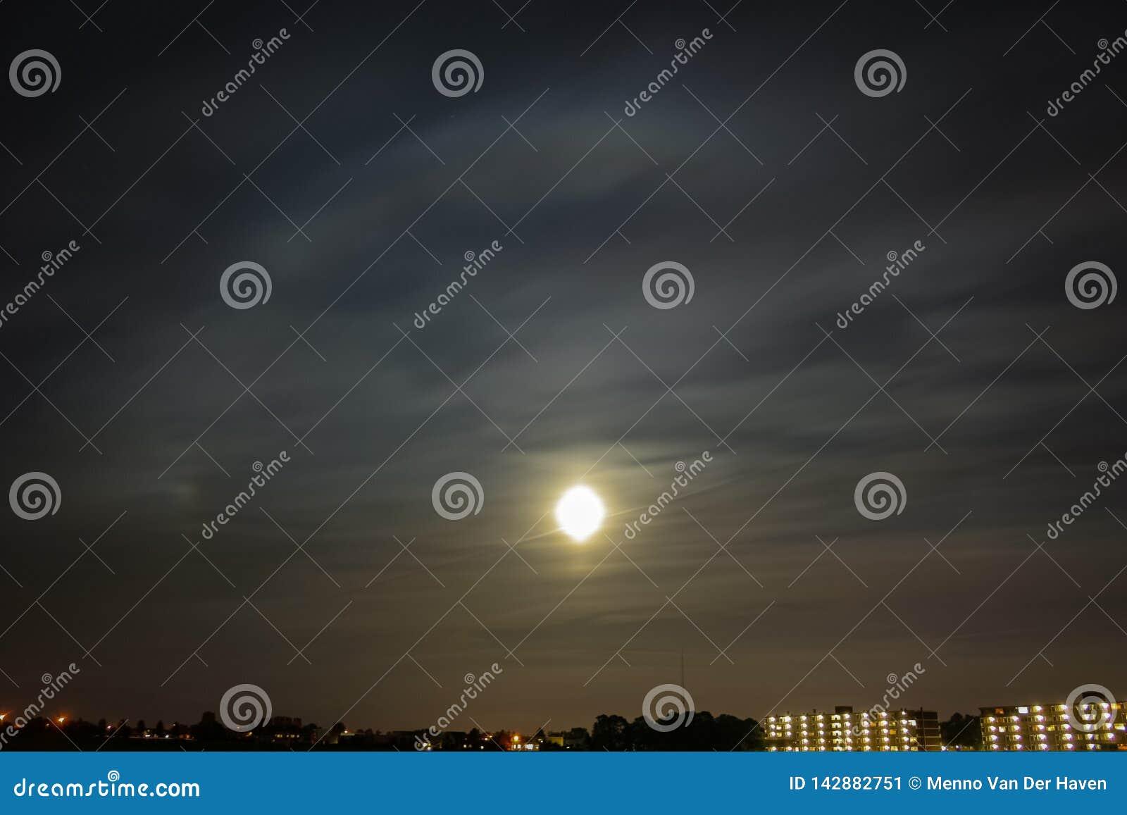 在月亮附近的明亮的圆光晕与parhelium到左边