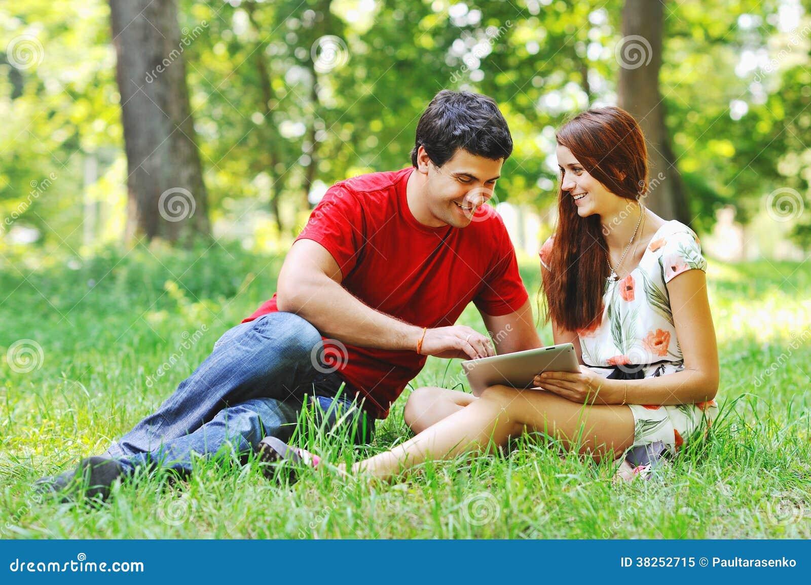 在有片剂计算机个人计算机的夏天公园结合一起放松