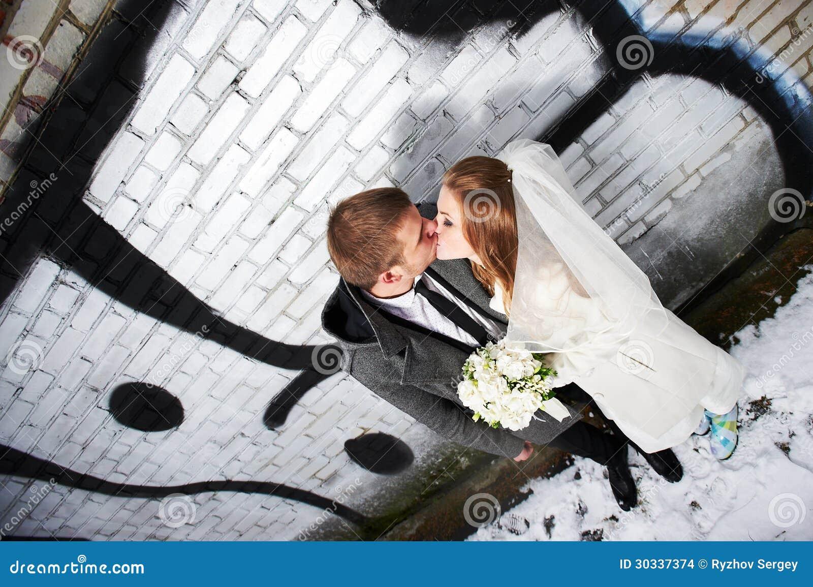 在有街道画的砖墙附近亲吻新娘和新郎