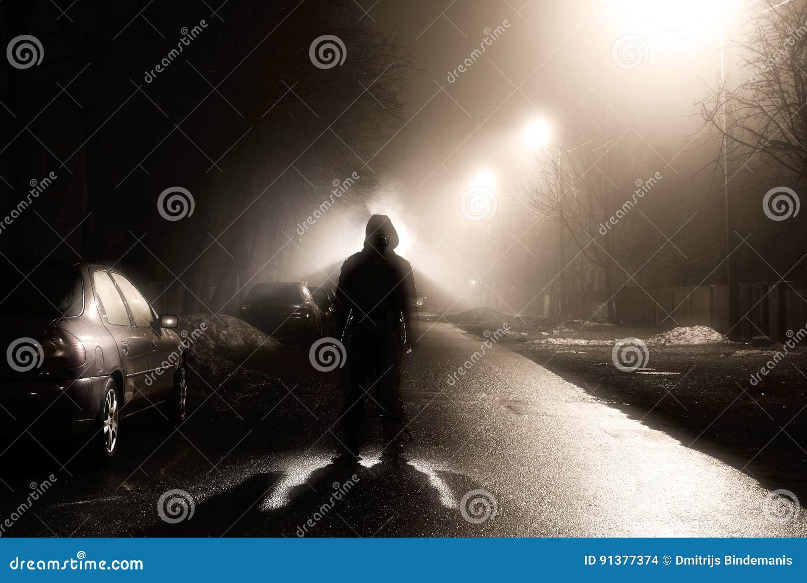在有雾的街道上的一个人在晚上