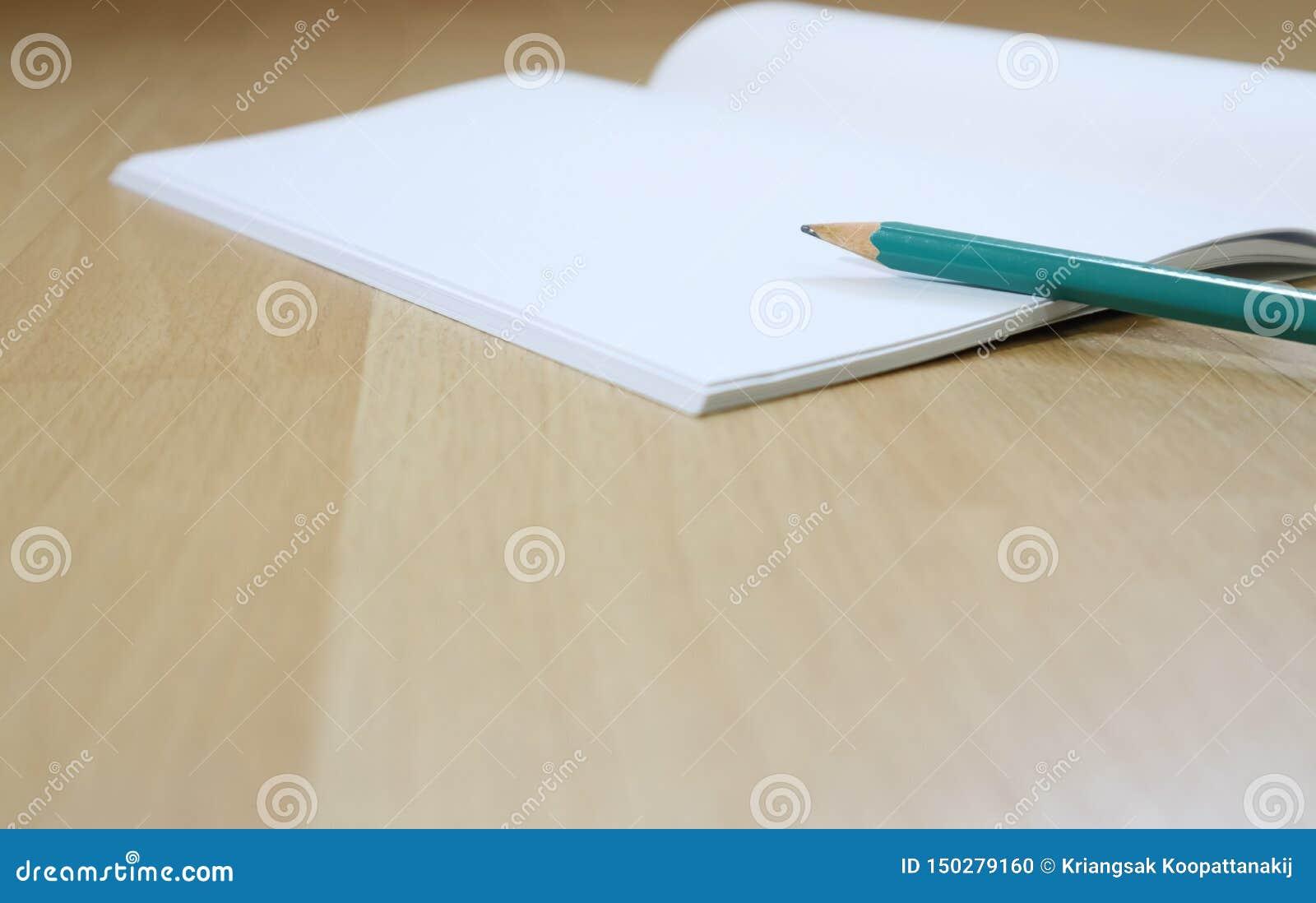在木地板上的笔记本和笔cil