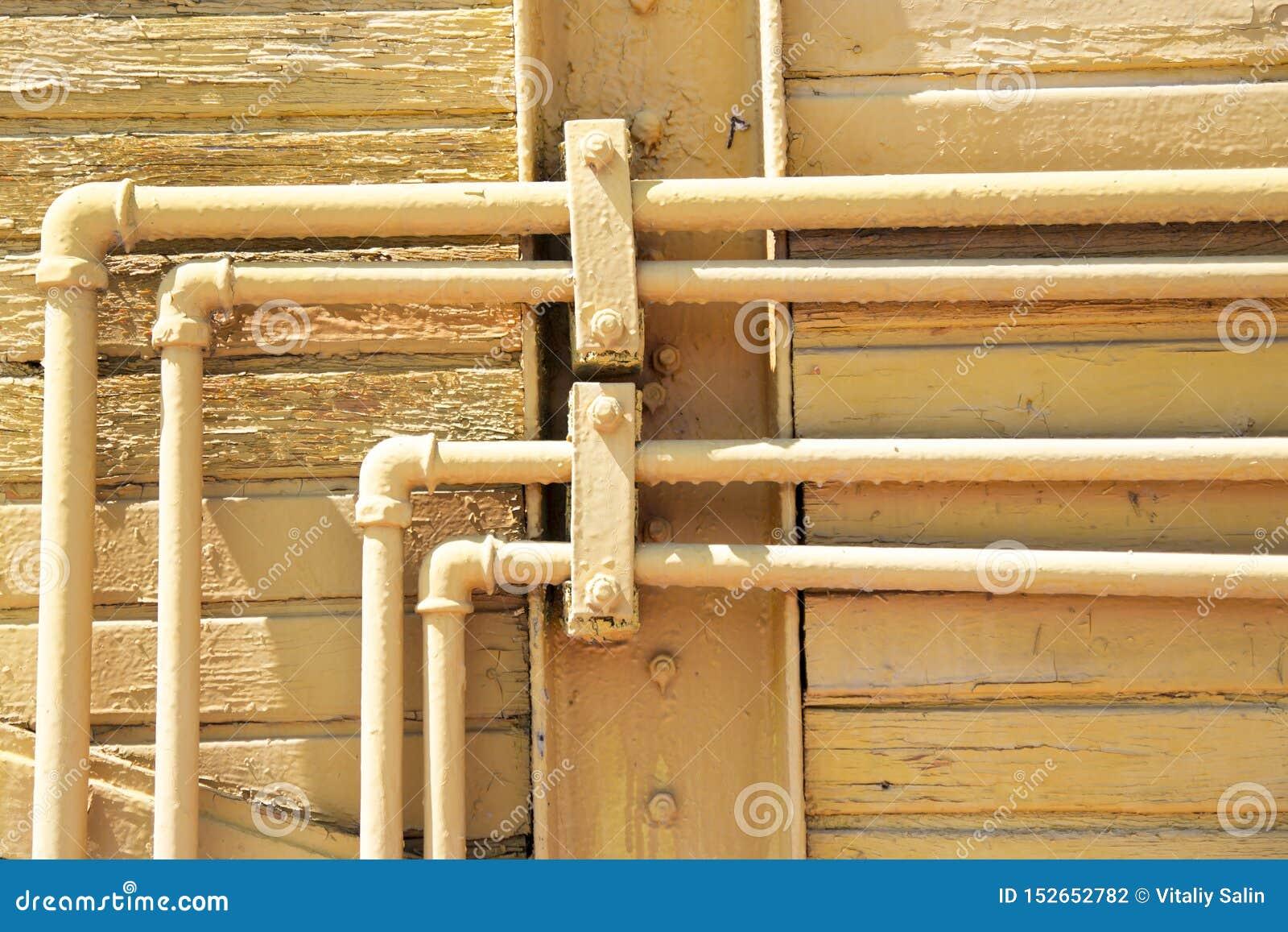 在木墙壁上的老黄色管子 抓痕难看的东西都市国家背景 为您的设计构造