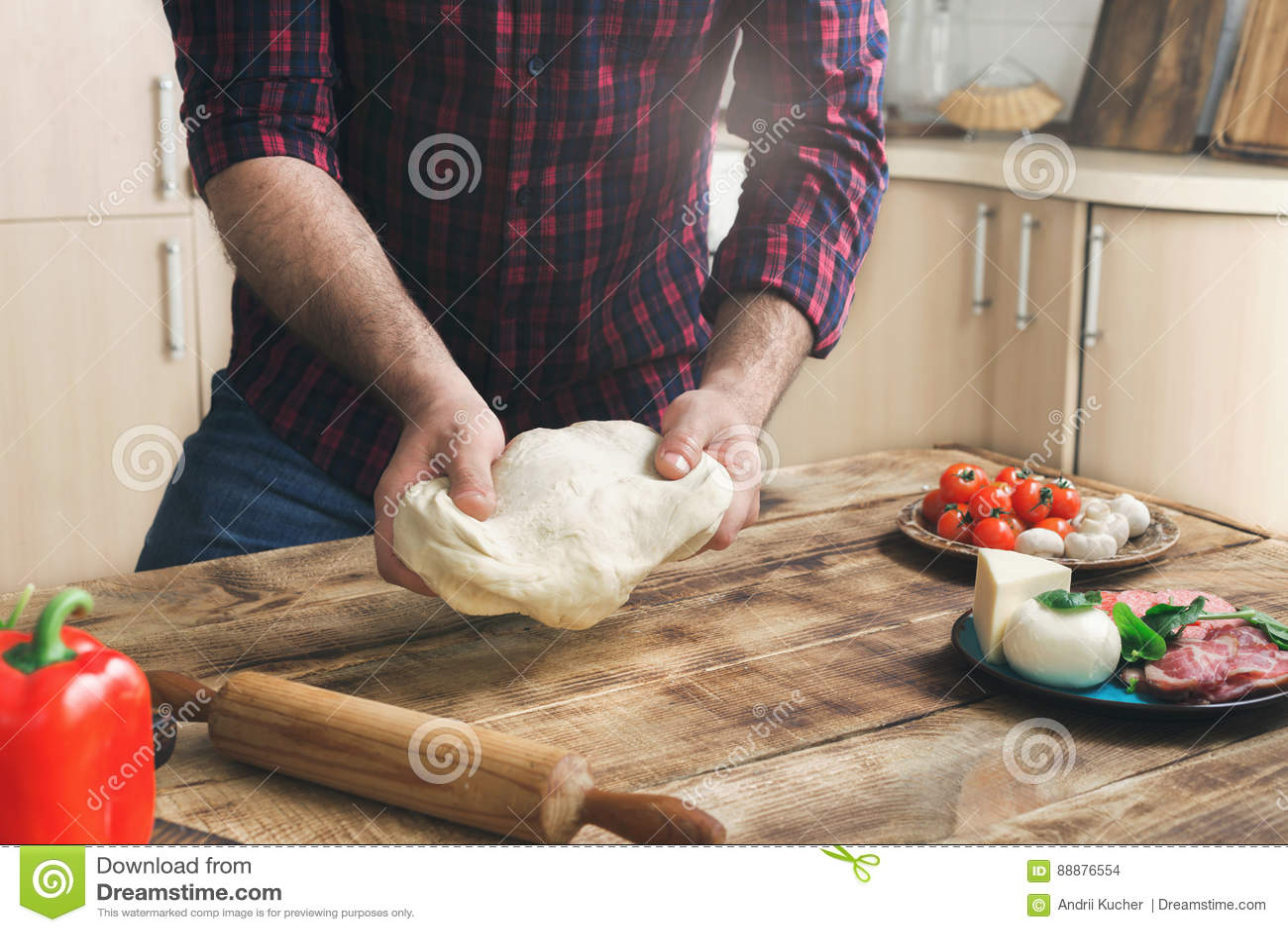 在木桌上的家庭厨房里供以人员准备薄饼