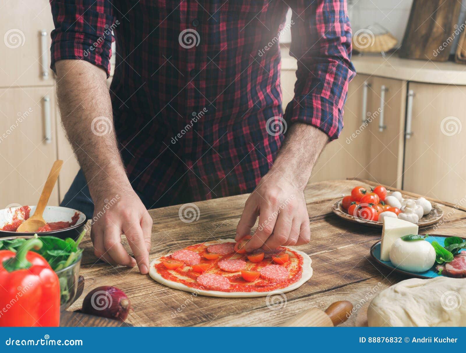 在木桌上的家庭厨房里供以人员烹调薄饼