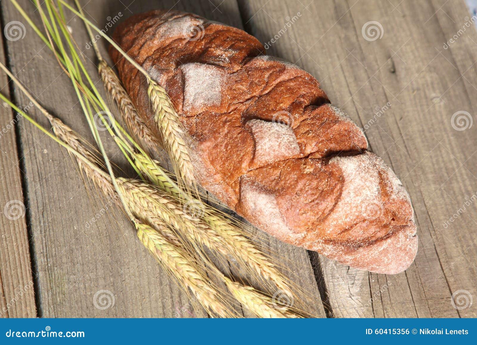 在木桌上的新近地被烘烤的传统面包