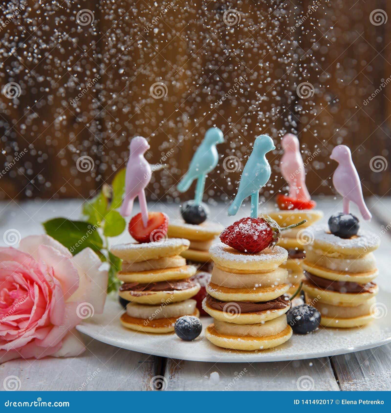 在白色木桌上的果子、莓果和薄煎饼点心