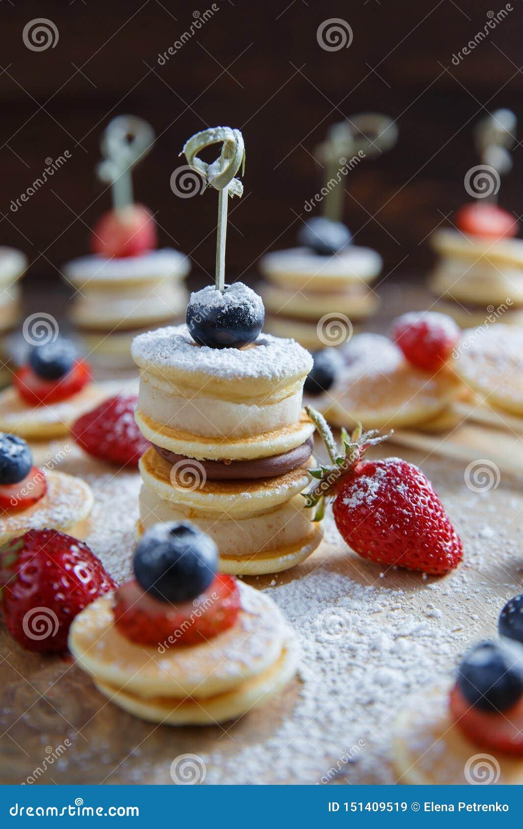 在木桌上的果子、莓果和薄煎饼点心
