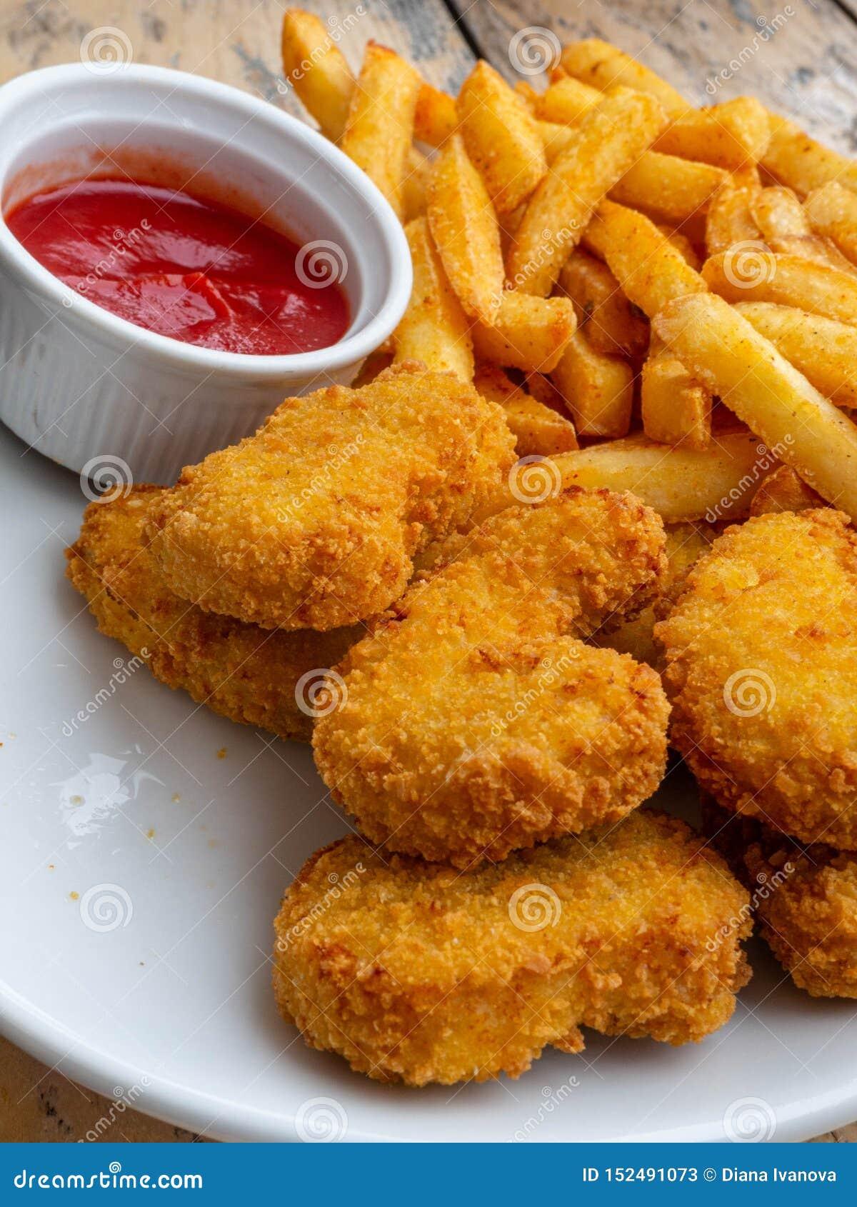 在木桌上的油煎的鸡翅 面包酥脆油煎的肯塔基鸡鲜美晚餐用西红柿酱