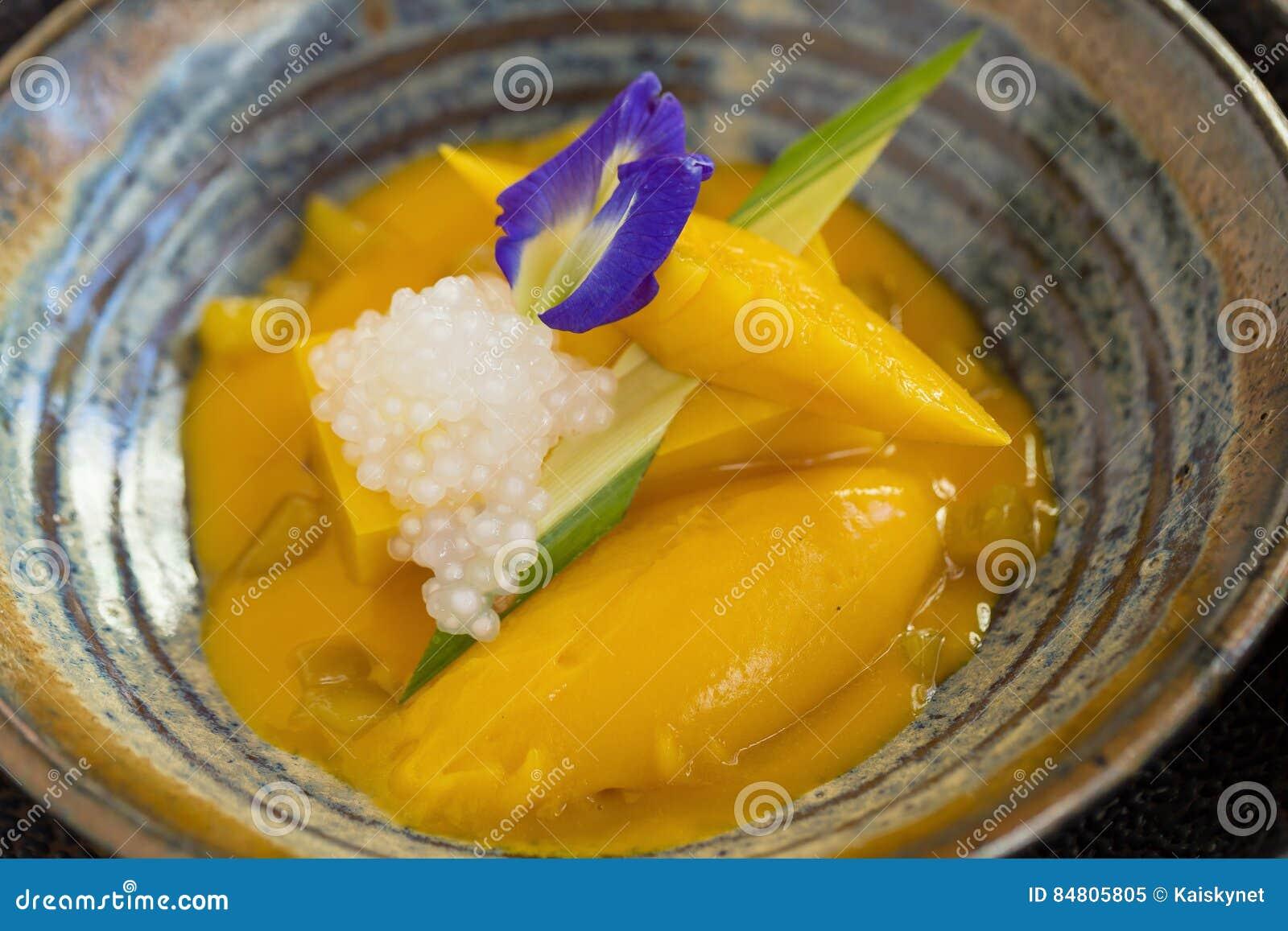 在木桌上的甜黄色芒果布丁