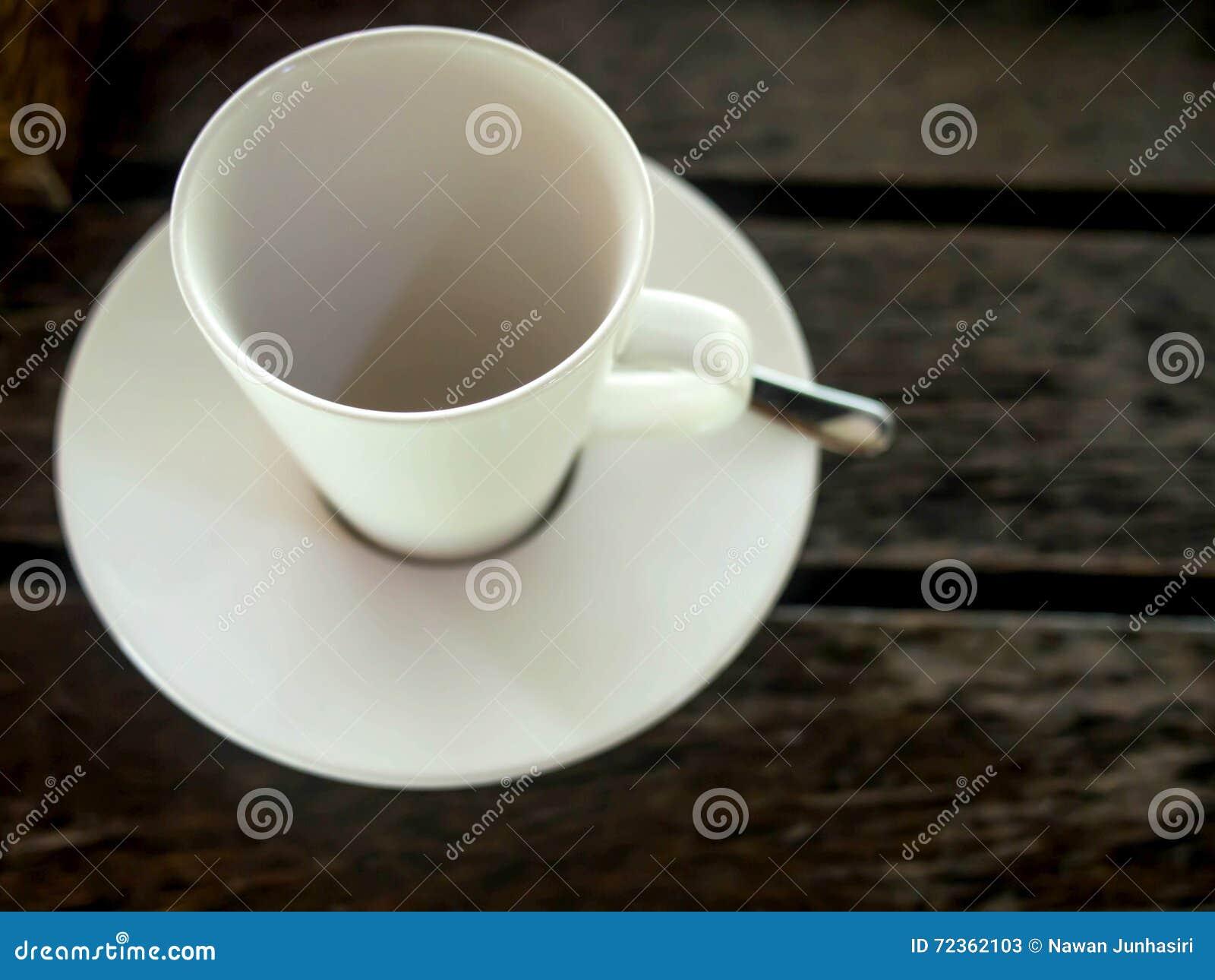 在木桌上的白色空的咖啡杯