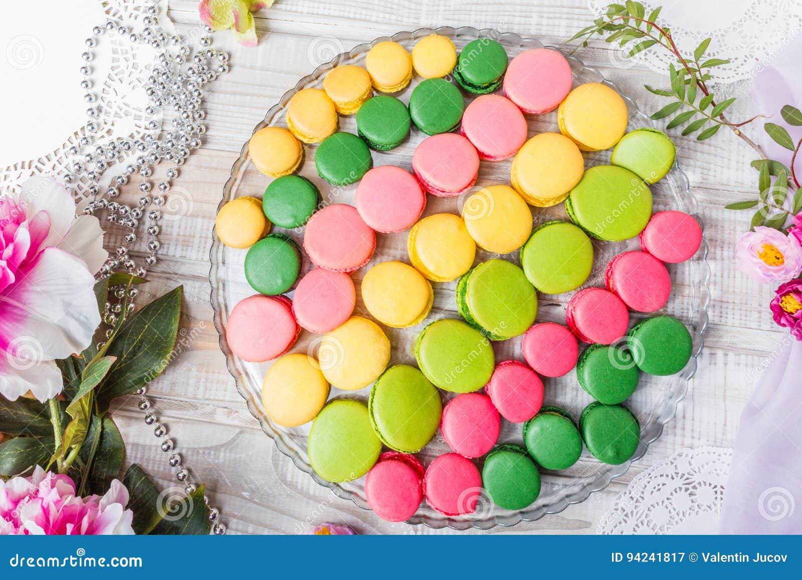 在木桌与花,法国甜纤巧,蛋白杏仁饼干纹理上的五颜六色的鲜美蛋白杏仁饼干 顶视图