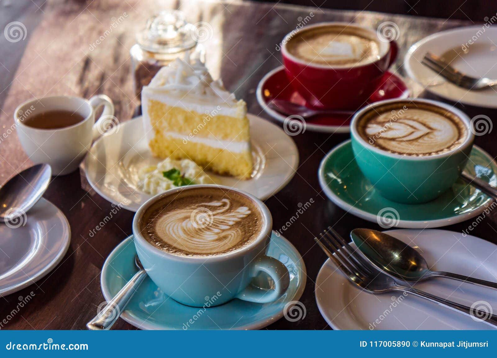 在木桌咖啡馆、饮料咖啡和鲜美蛋糕的咖啡时间