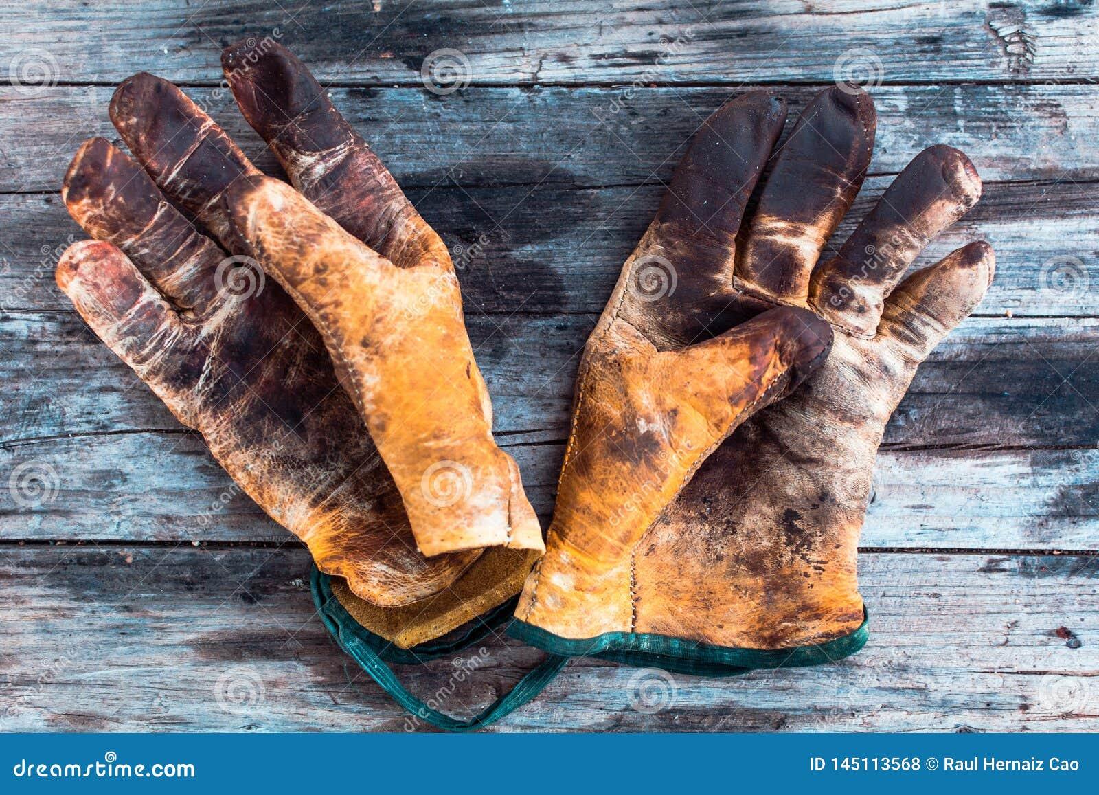 在木桌的老和肮脏的运作的手套,每个手指的手套
