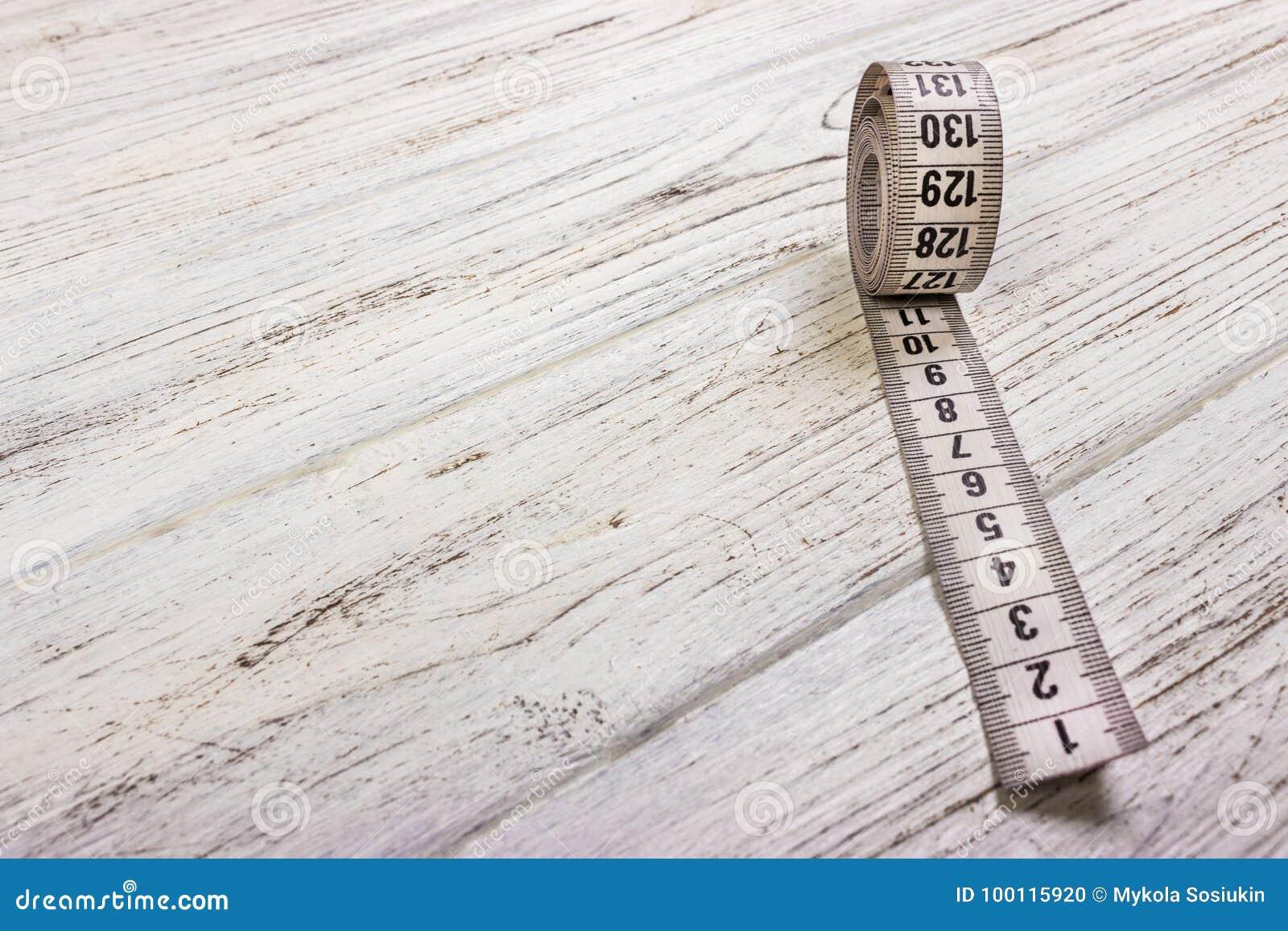 在木桌背景的关闭裁缝测量的磁带 白色测量的磁带浅dept领域