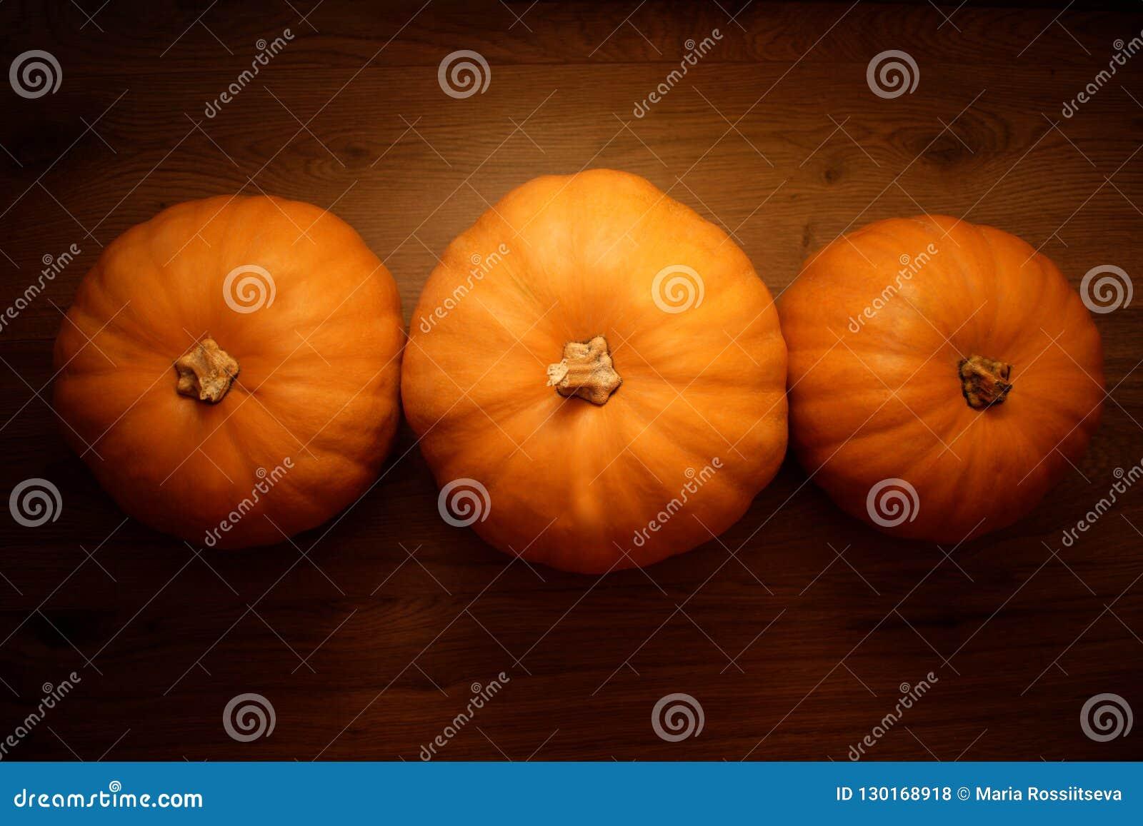 在木背景的三个橙色南瓜
