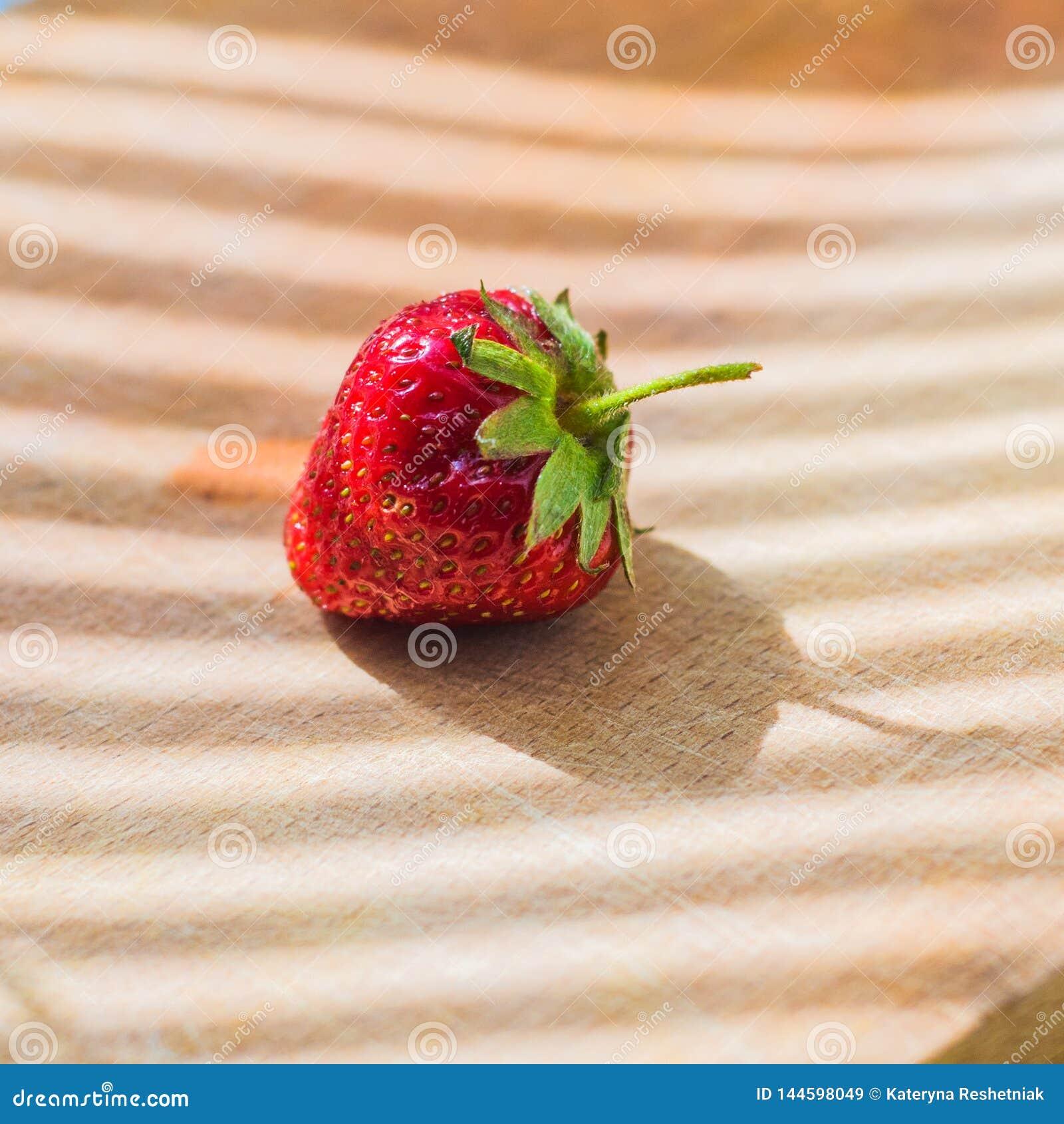 在木背景的水多的新鲜的草莓
