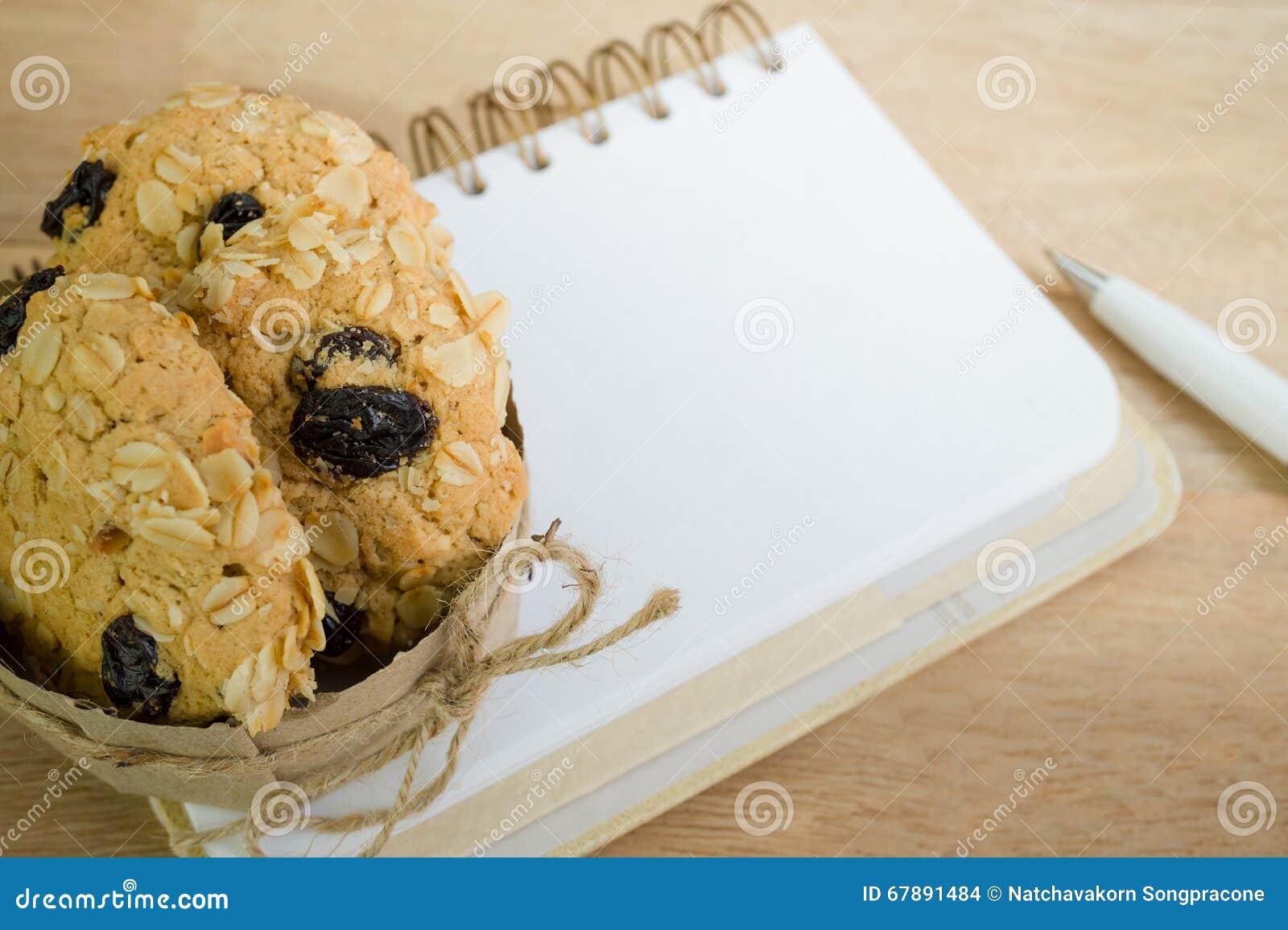 在木背景的空白的笔记本和燕麦曲奇饼