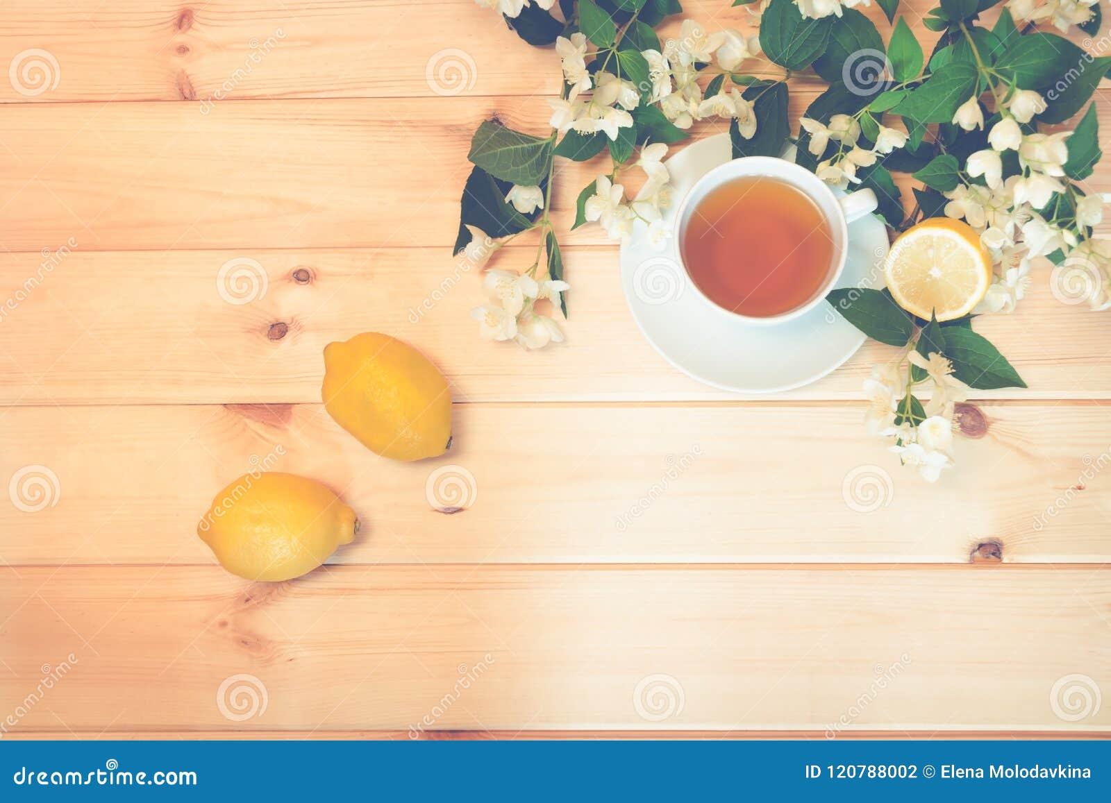 在木背景的绿茶、柠檬和茉莉花花