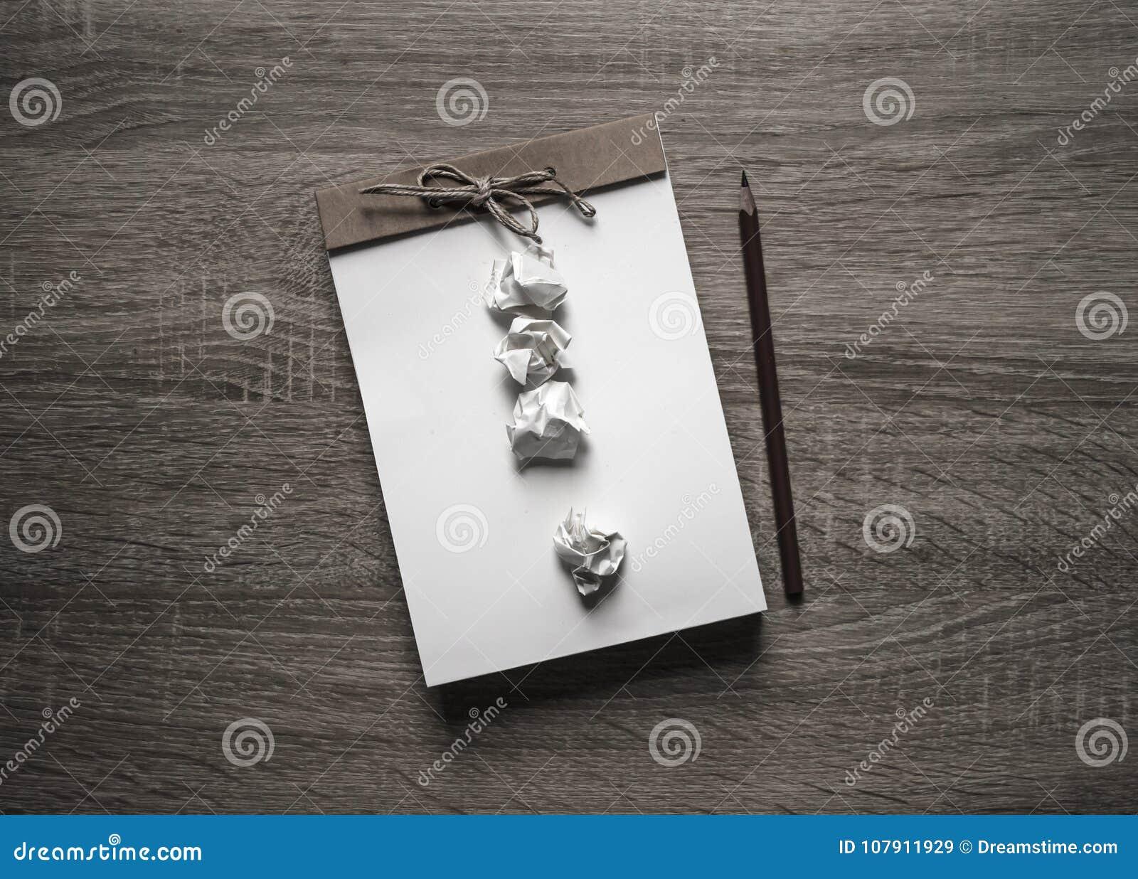 在木背景说谎在笔记薄惊叹号的一支工艺笔记薄scrapbooking的铅笔从被弄皱的纸