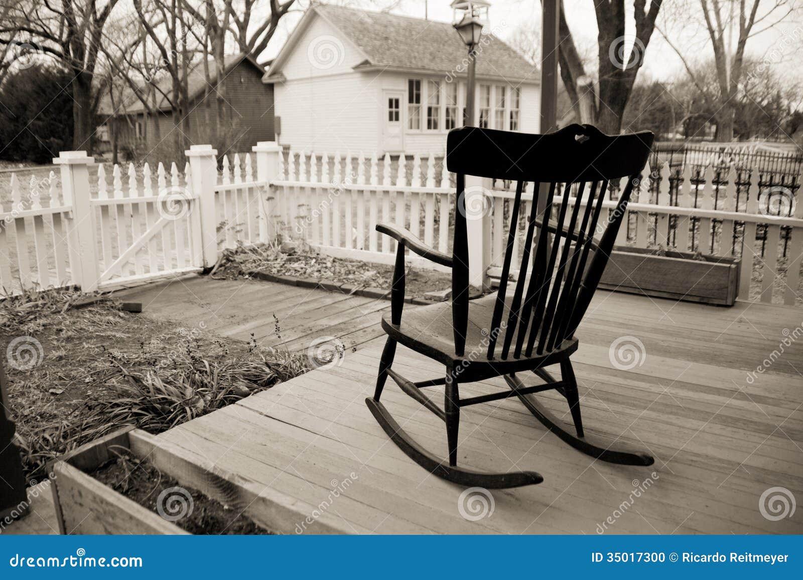 在木门廊的老摇椅与白色尖桩篱栅。