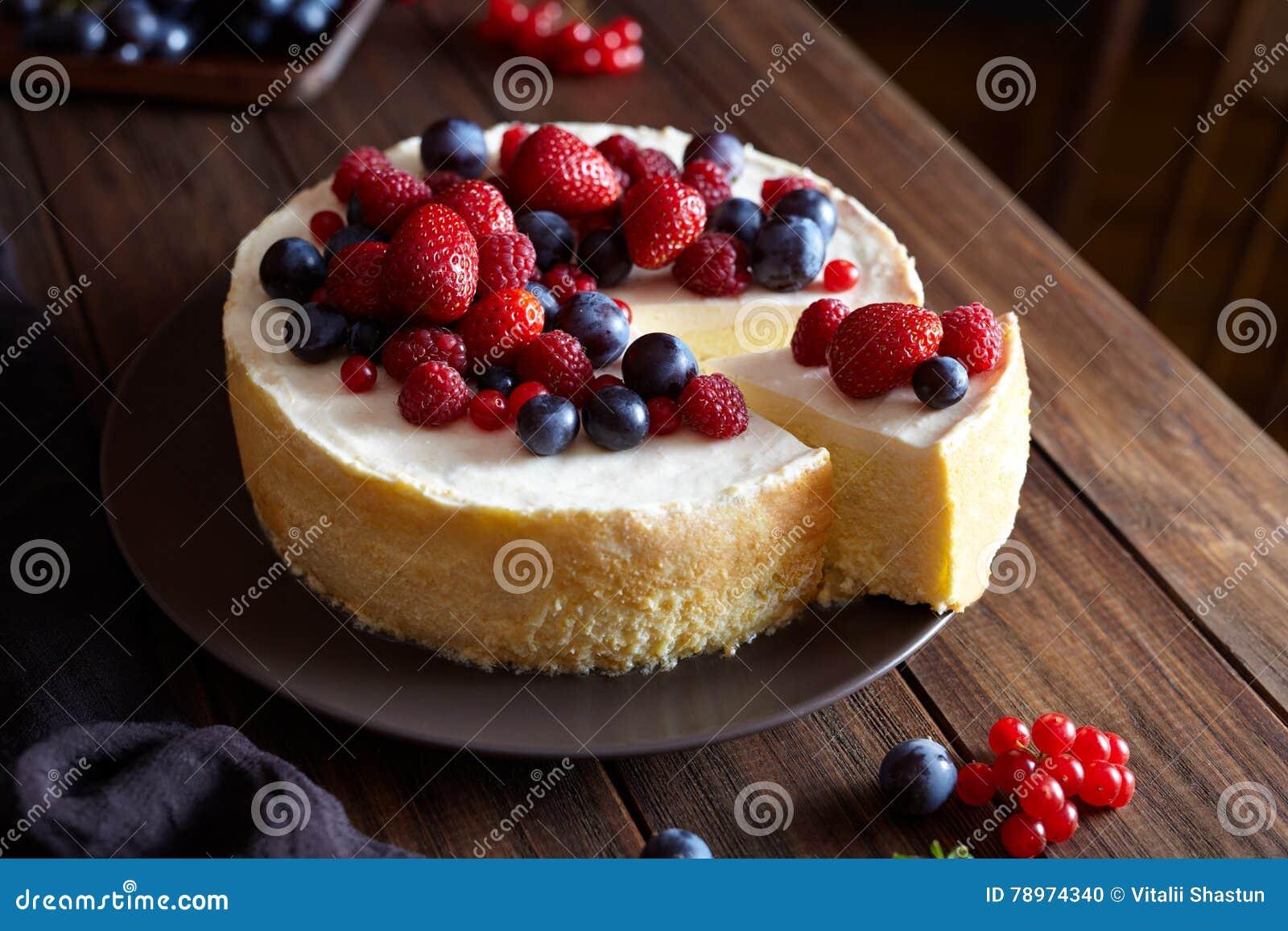 在木黑暗的桌上的自创圣诞节冬天莓果乳酪蛋糕 乳脂状的mascarpone点心