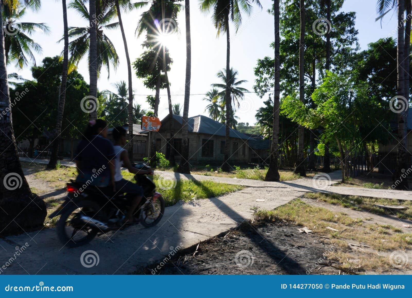 在村庄路的一辆夫妇乘驾摩托车