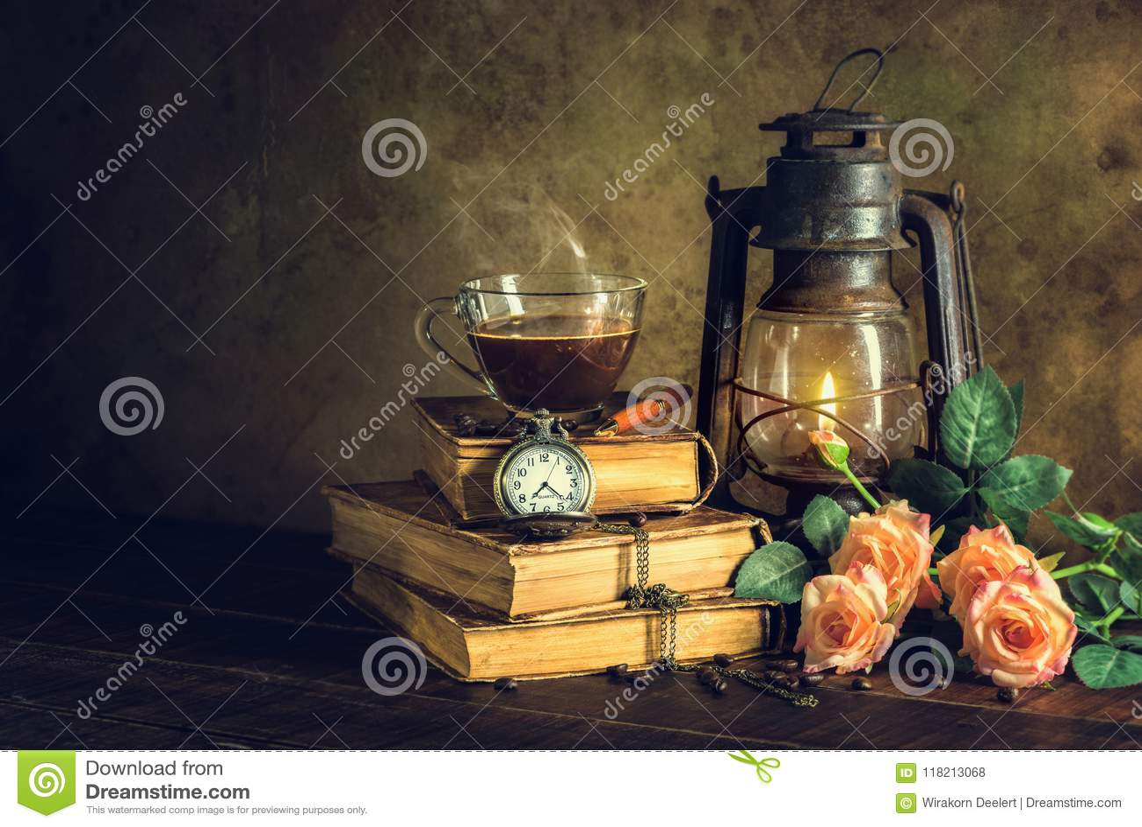 在杯子玻璃的咖啡在旧书和与煤油灯的时钟葡萄酒上油烧与在年迈的木地板上的焕发柔光的灯笼