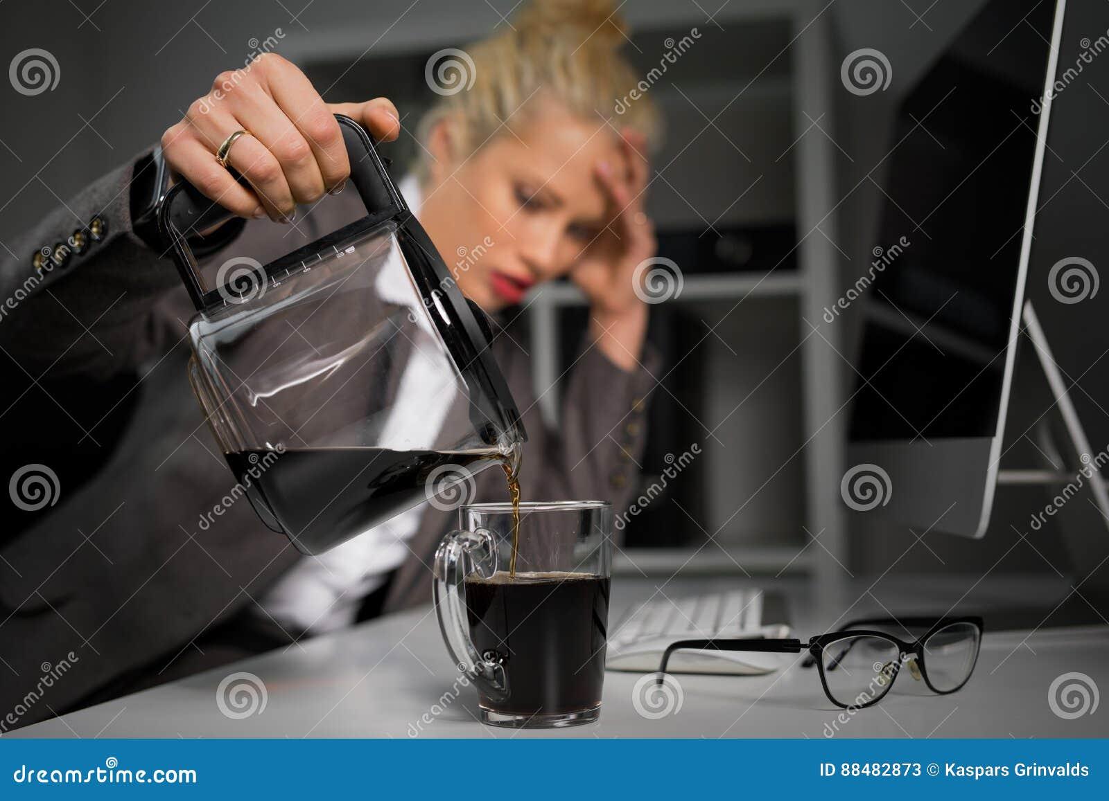 在杯子的妇女倾吐的咖啡