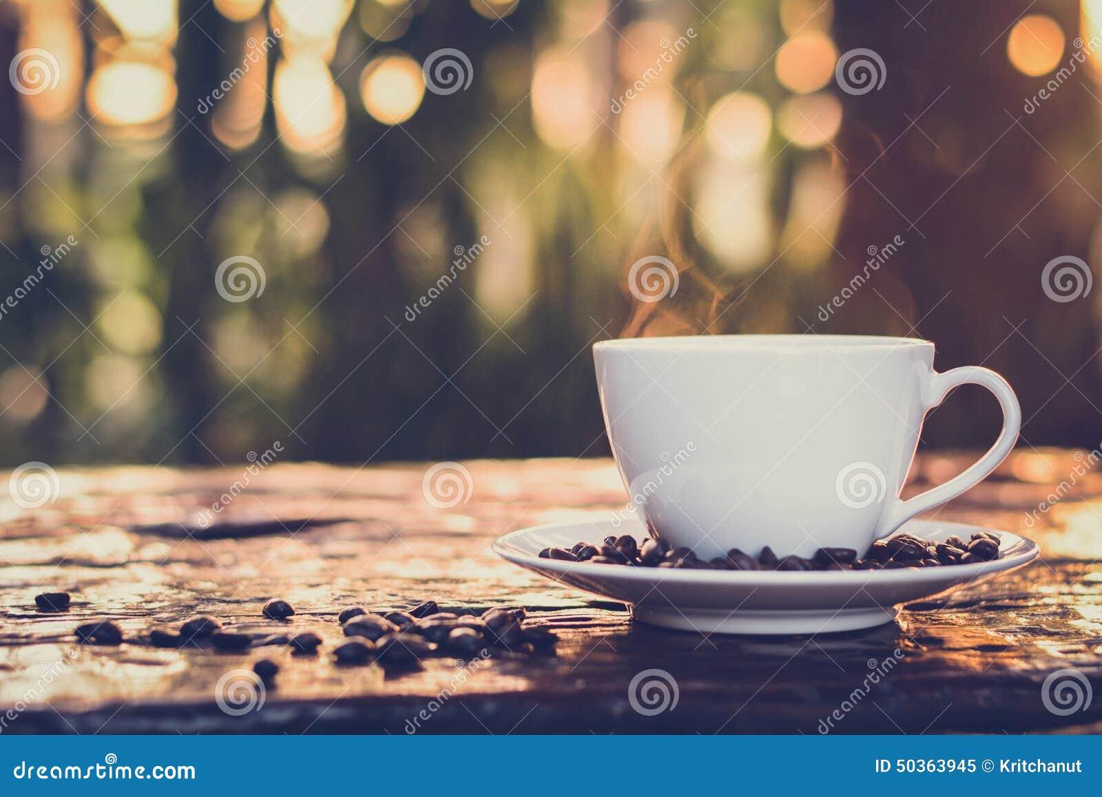 在杯子的热的咖啡在老木桌上有迷离深绿自然背景