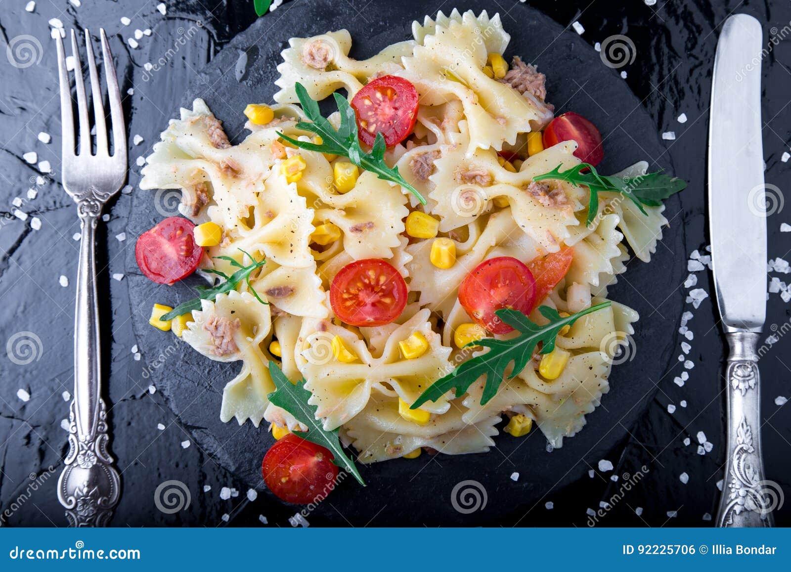 在板岩板材的意大利面制色拉用在刀子和匙子附近的蕃茄樱桃、金枪鱼、玉米和芝麻菜 顶视图 成份 烹调意大利语的食品成分