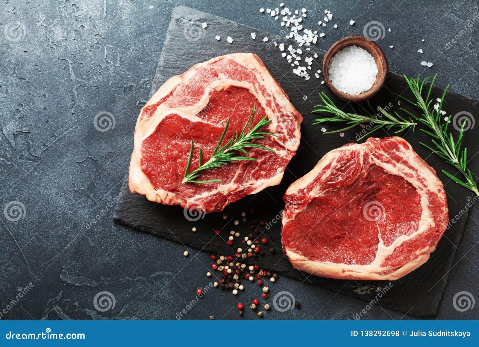 在板岩黑色委员会顶视图的新鲜的肉 未加工的牛排和香料烹调的