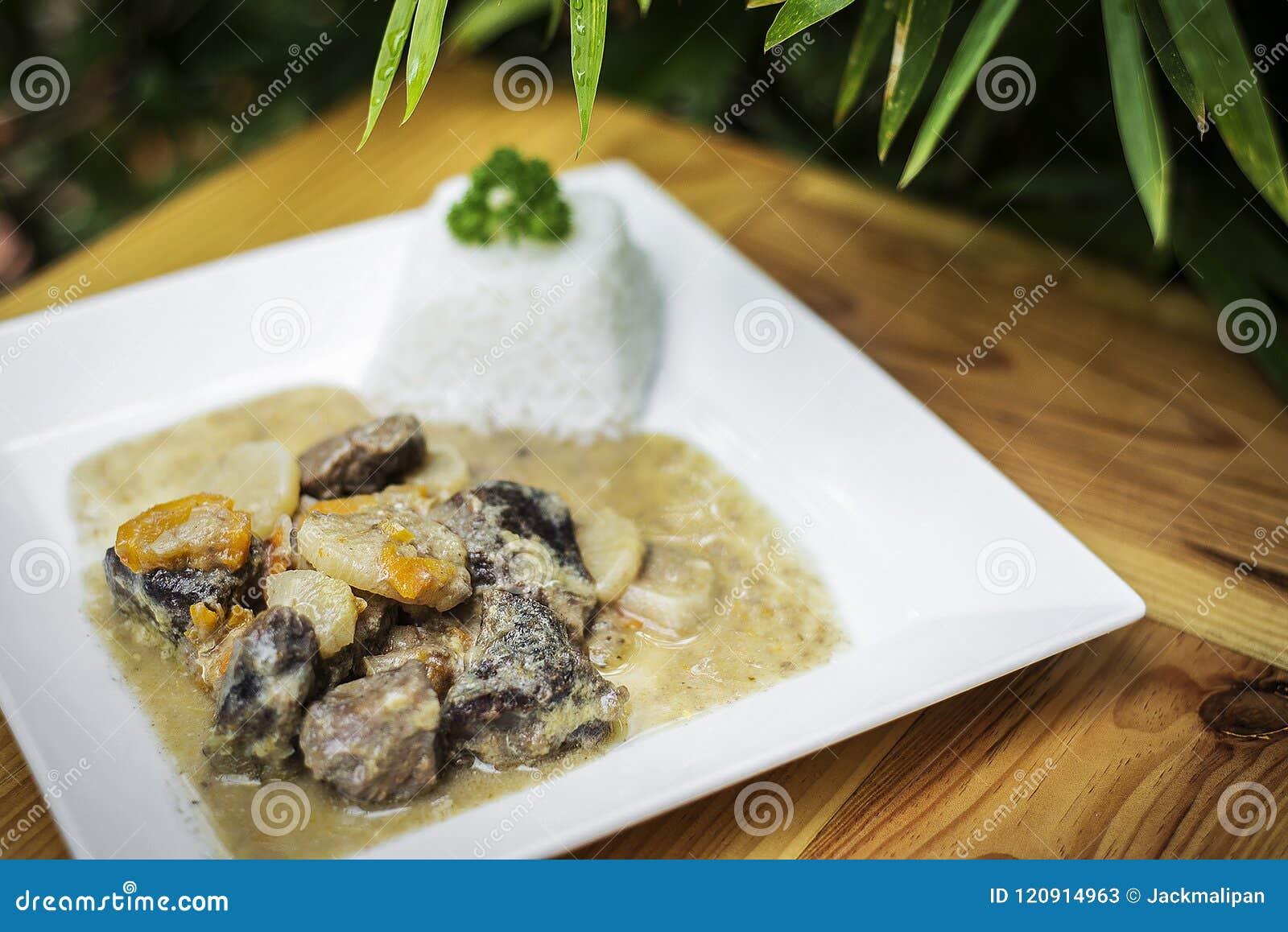 在板材的有机牛肉和德国泡菜奶油色菜炖煮的食物