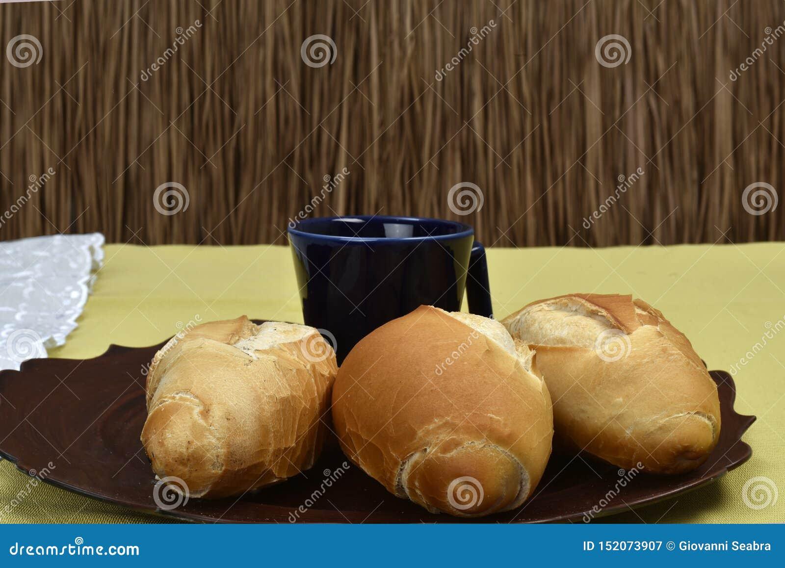 在板材的法式面包有黑杯子的在背景中