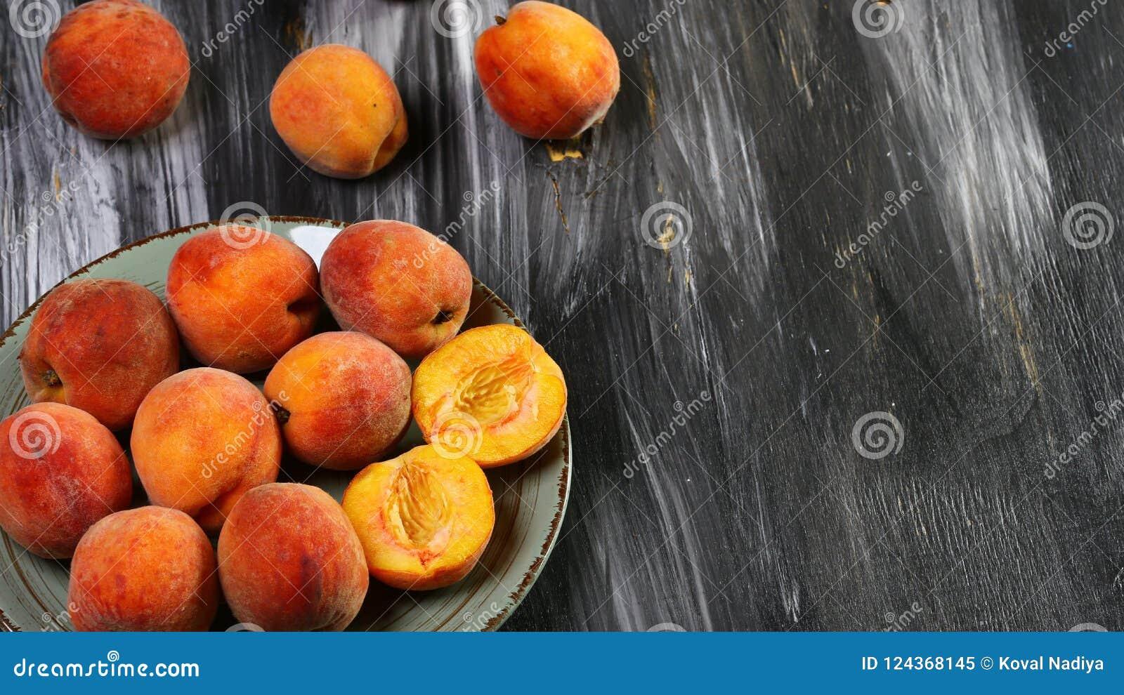 在板材的甜新鲜的桃子 在黑桌上 复制空间 平的位置 顶视图