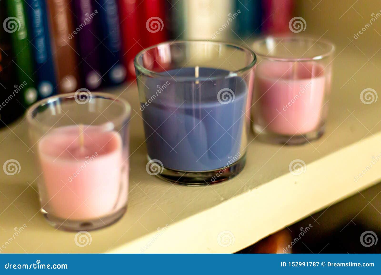 在架子的三个蜡烛与背景书
