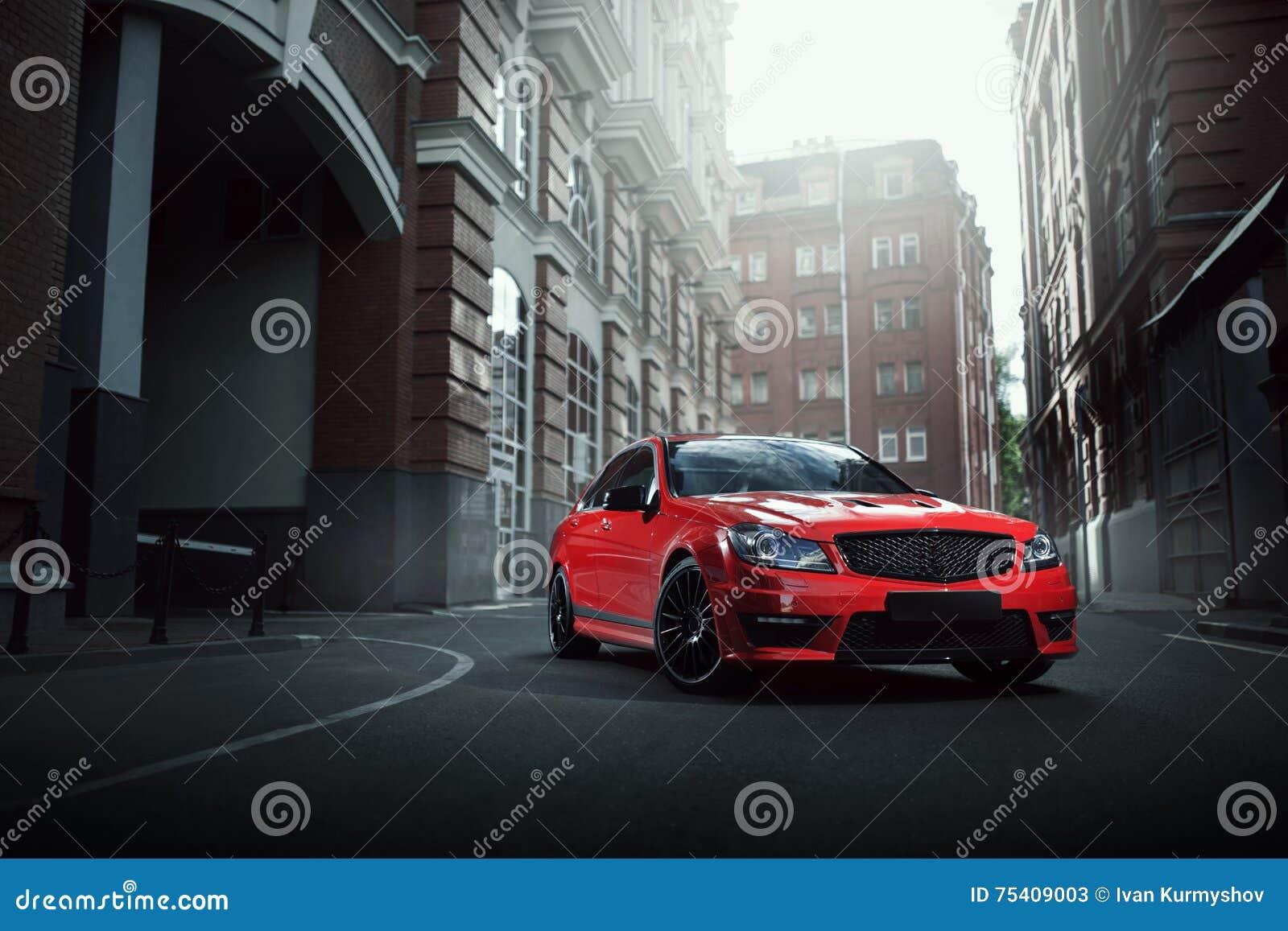 在柏油路的红色汽车逗留在白天的城市
