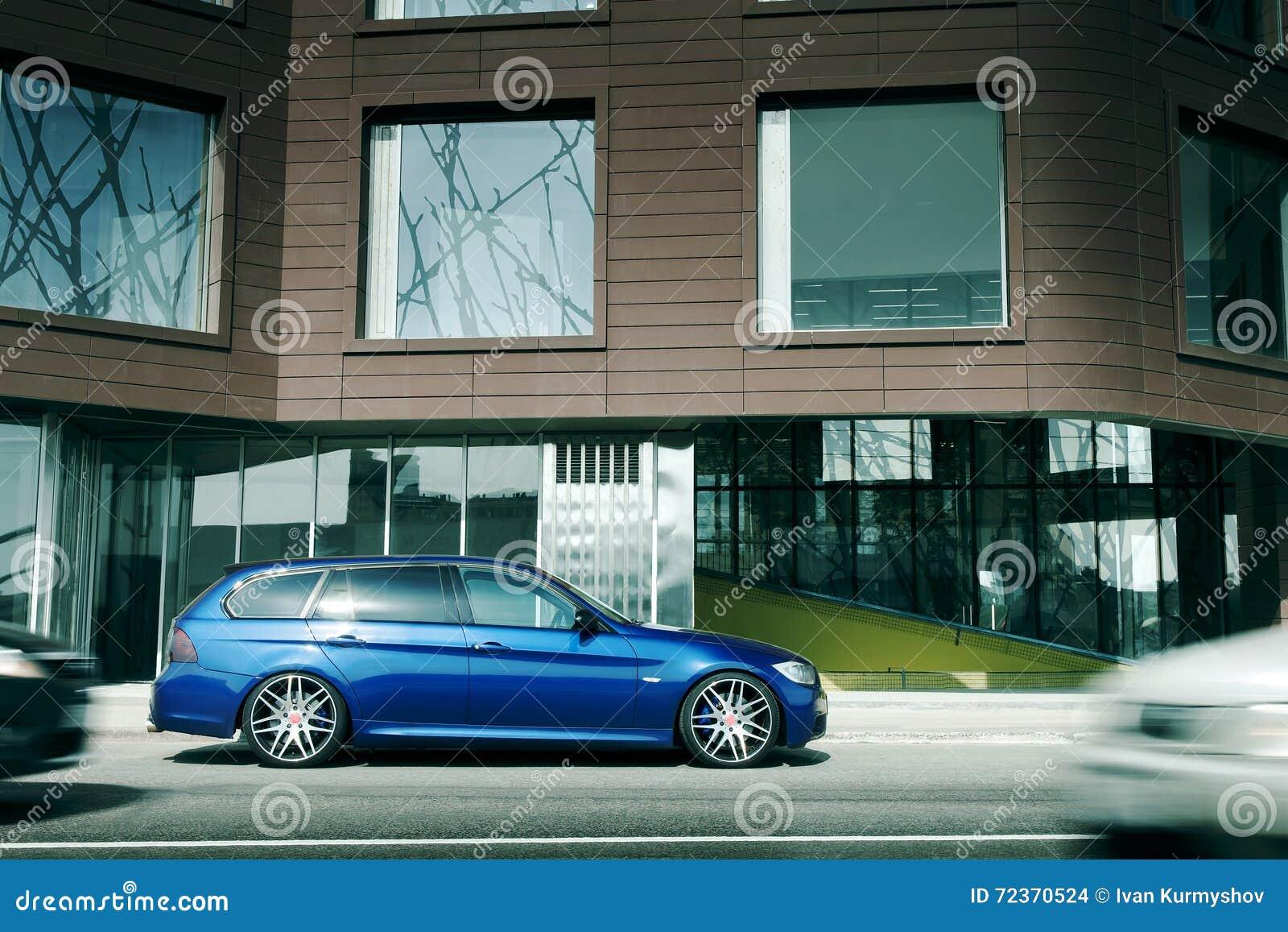 在柏油路的蓝色汽车逗留在城市