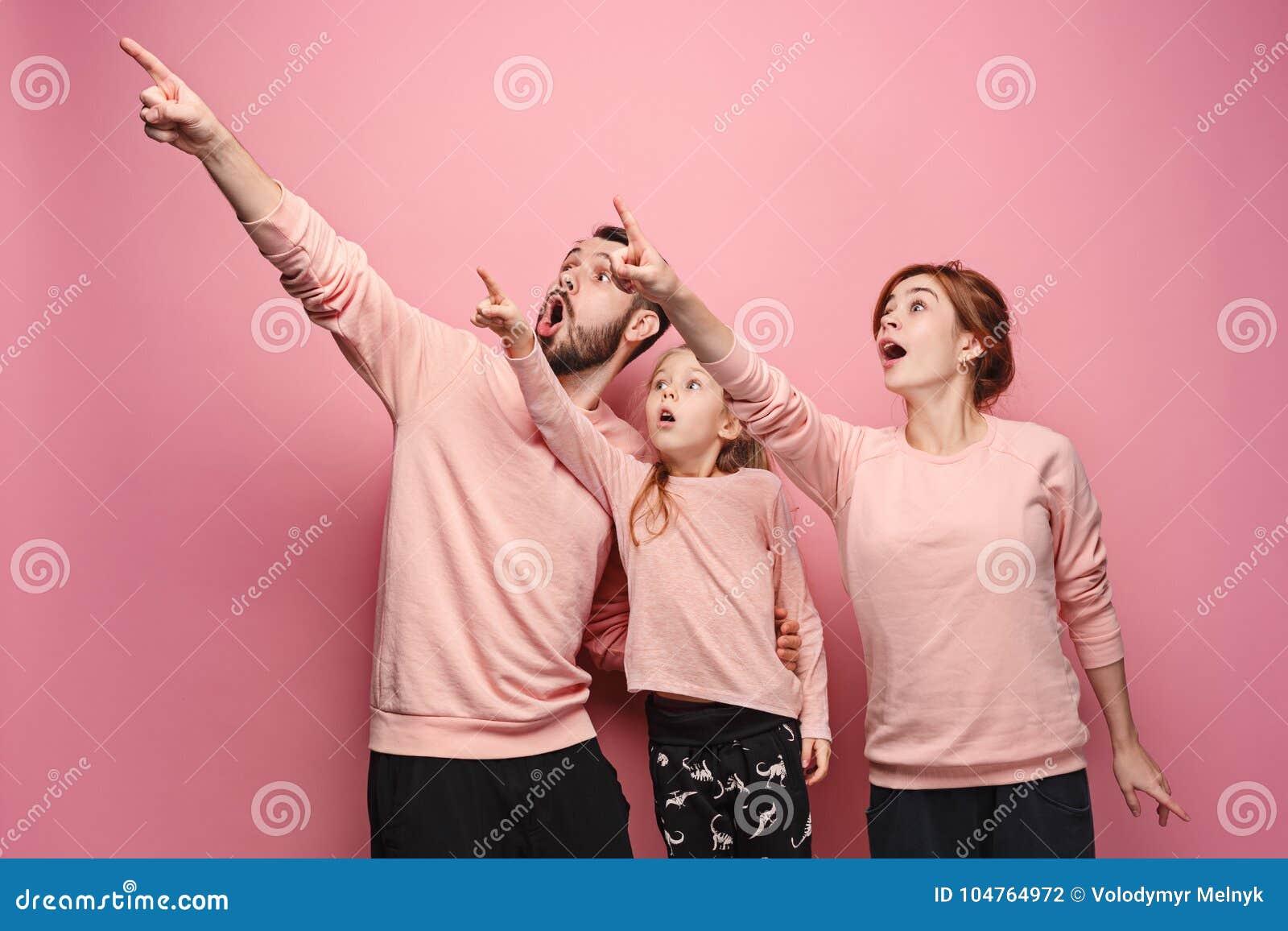 在桃红色的惊奇的年轻家庭