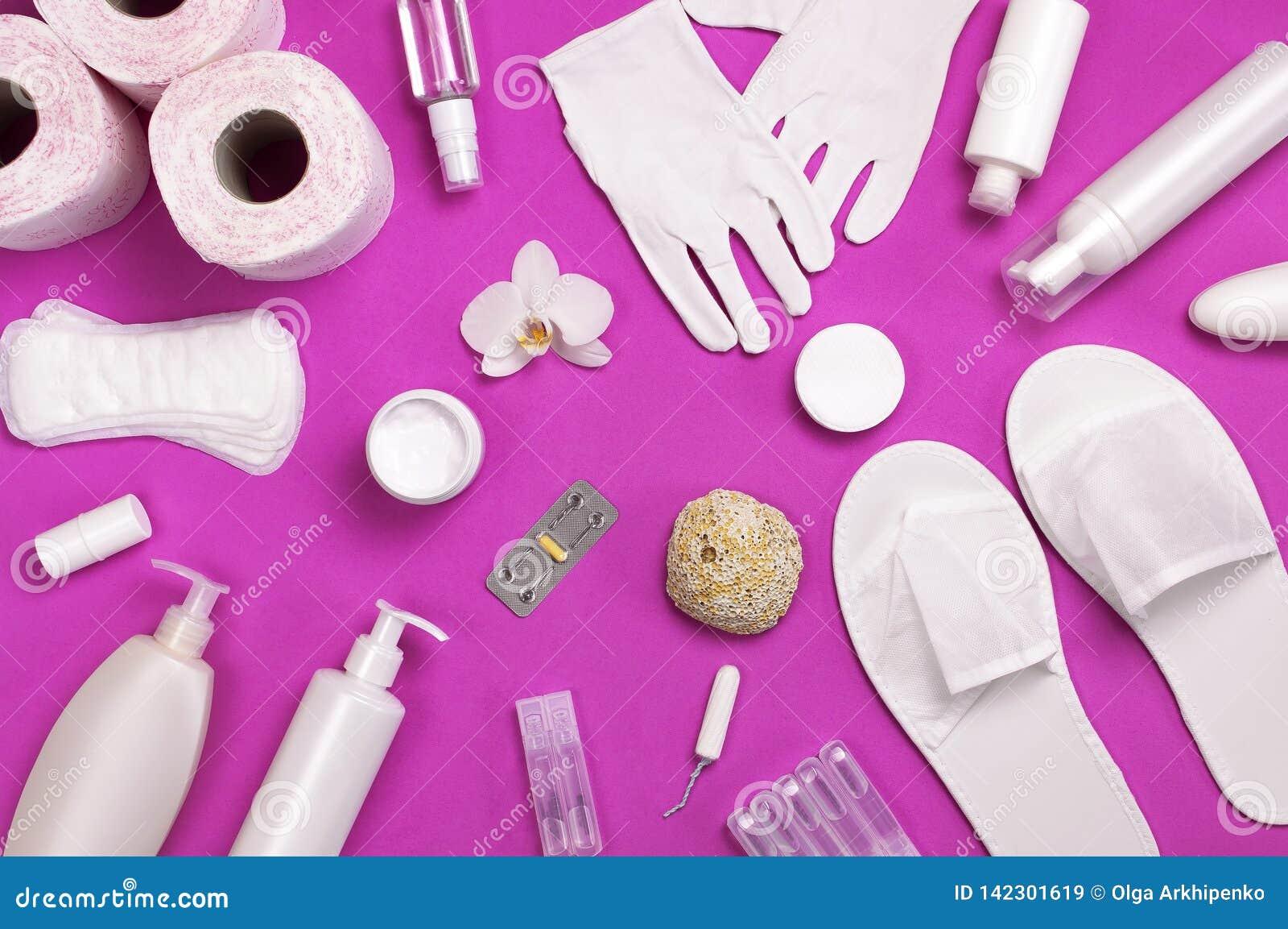 在桃红色的白色化妆瓶容器手套拖鞋卫生学项目垫圈棉塞化装棉手纸片剂兰花花