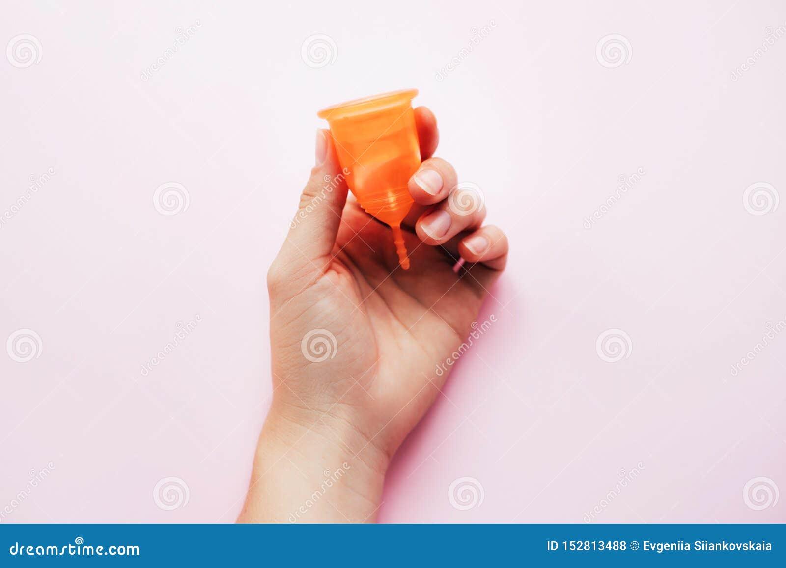 在桃红色背景的妇女的手藏品月经杯子