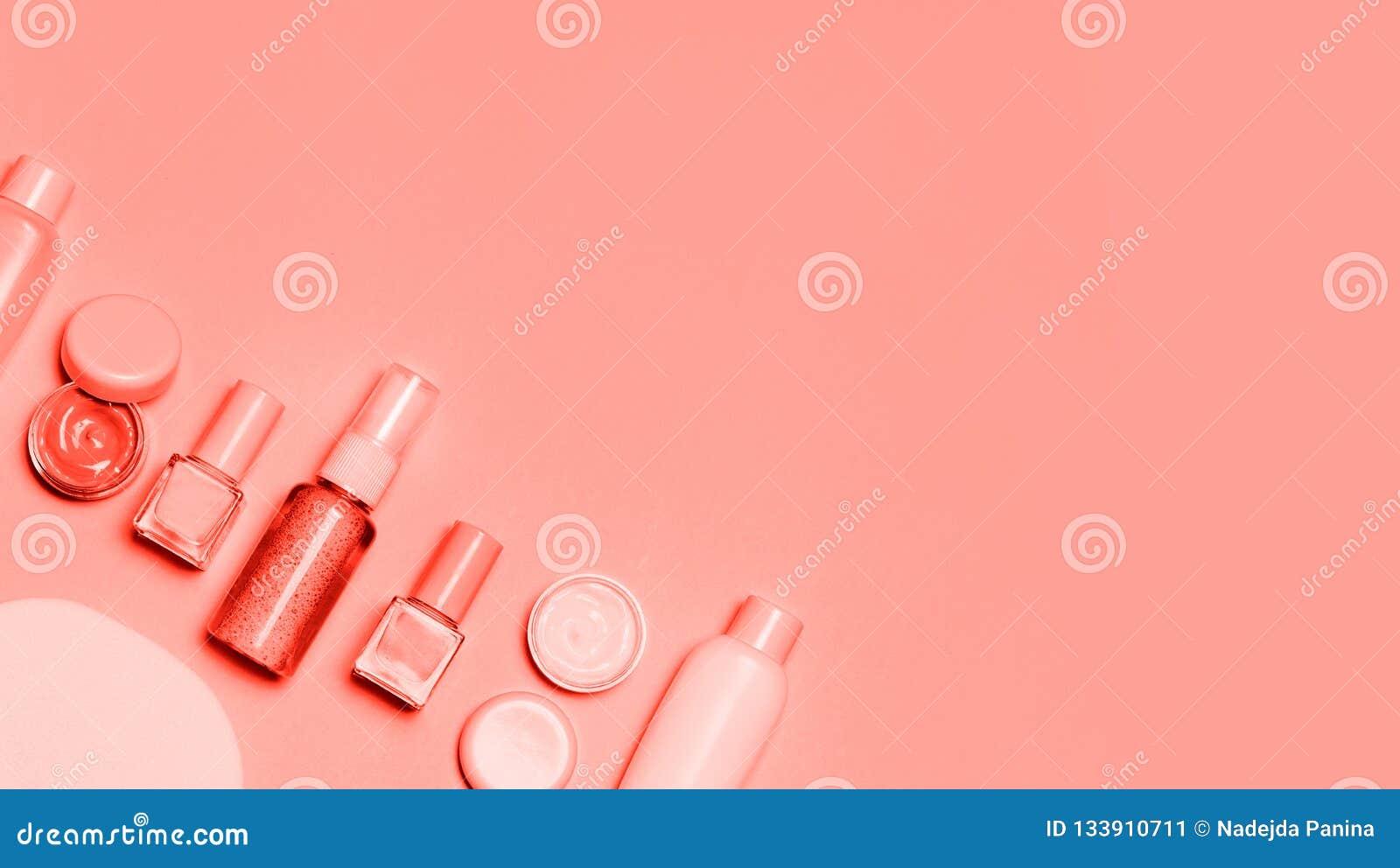 在桃红色背景的居住的珊瑚装饰化妆用品