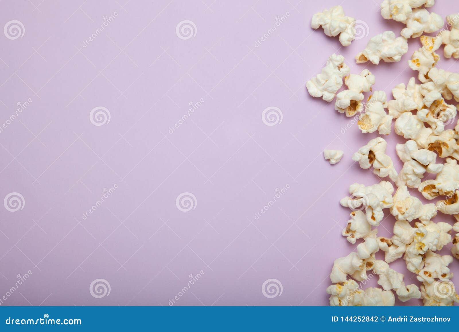 在桃红色背景的溢出的玉米花,文本的空的空间