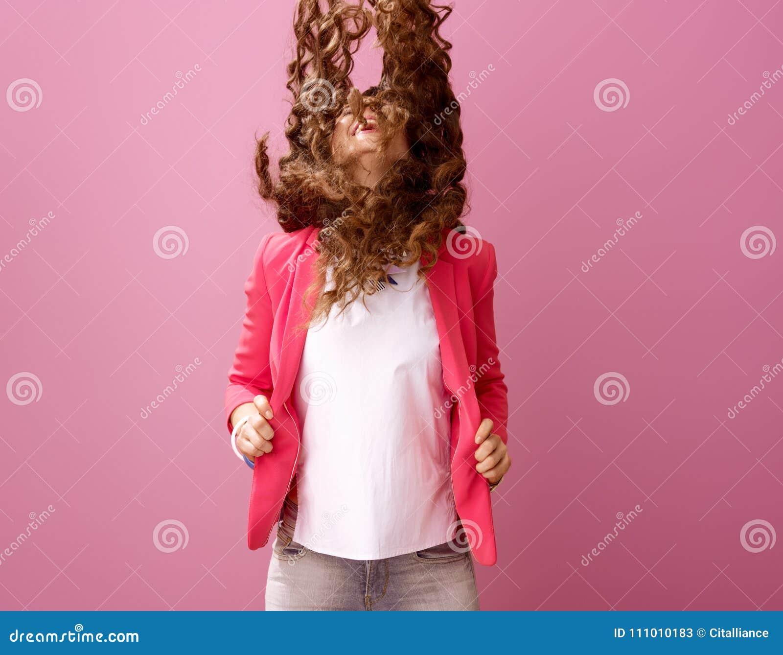 在桃红色背景隔绝的微笑的现代妇女震动头发
