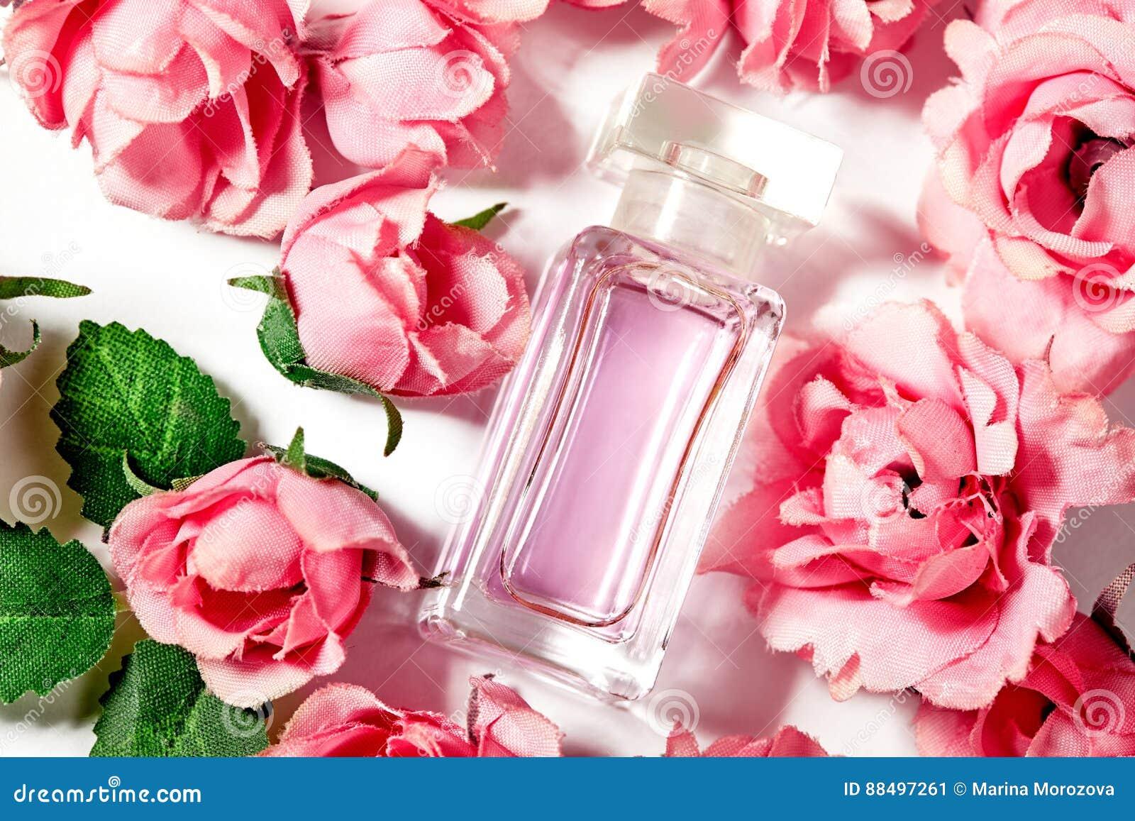 在桃红色花玫瑰的香水瓶 与豪华芳香parfume的春天背景 秀丽化妆用品射击