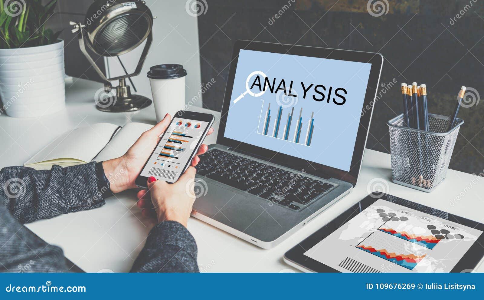 在桌上是膝上型计算机、数字式片剂有图的,图表和图在屏幕上